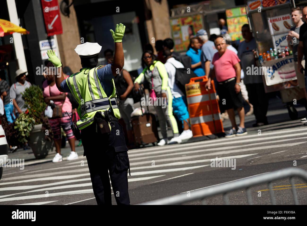 Donna di polizia dirigere traffico nei pressi di Herald Square nel centro cittadino di Manhattan, New York City, Immagini Stock