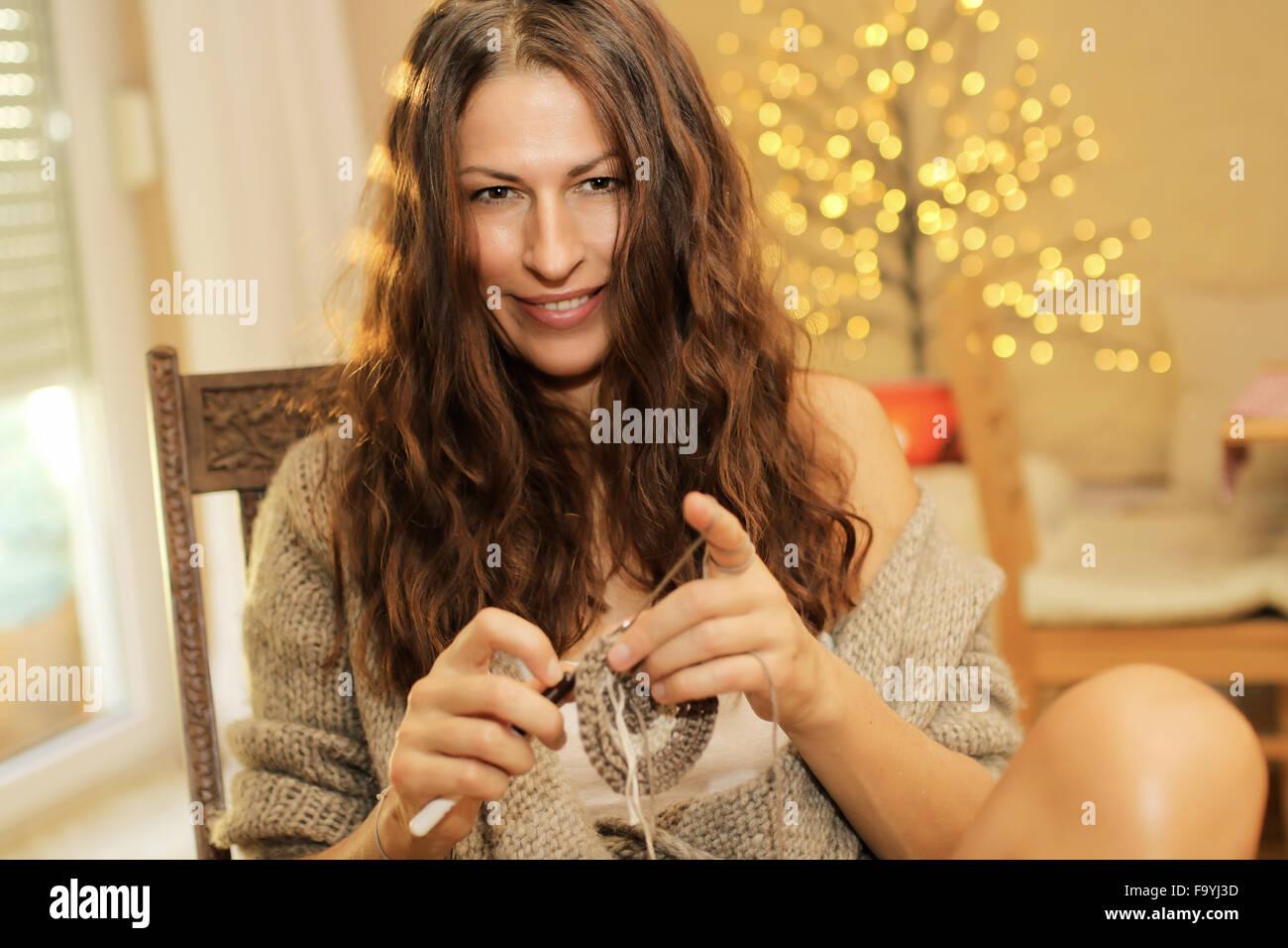 La donna in una sedia a dondolo, uncinetto e sorridente sul dicembre 08, 2015 a Monaco di Baviera, Germania. Modello Foto Stock