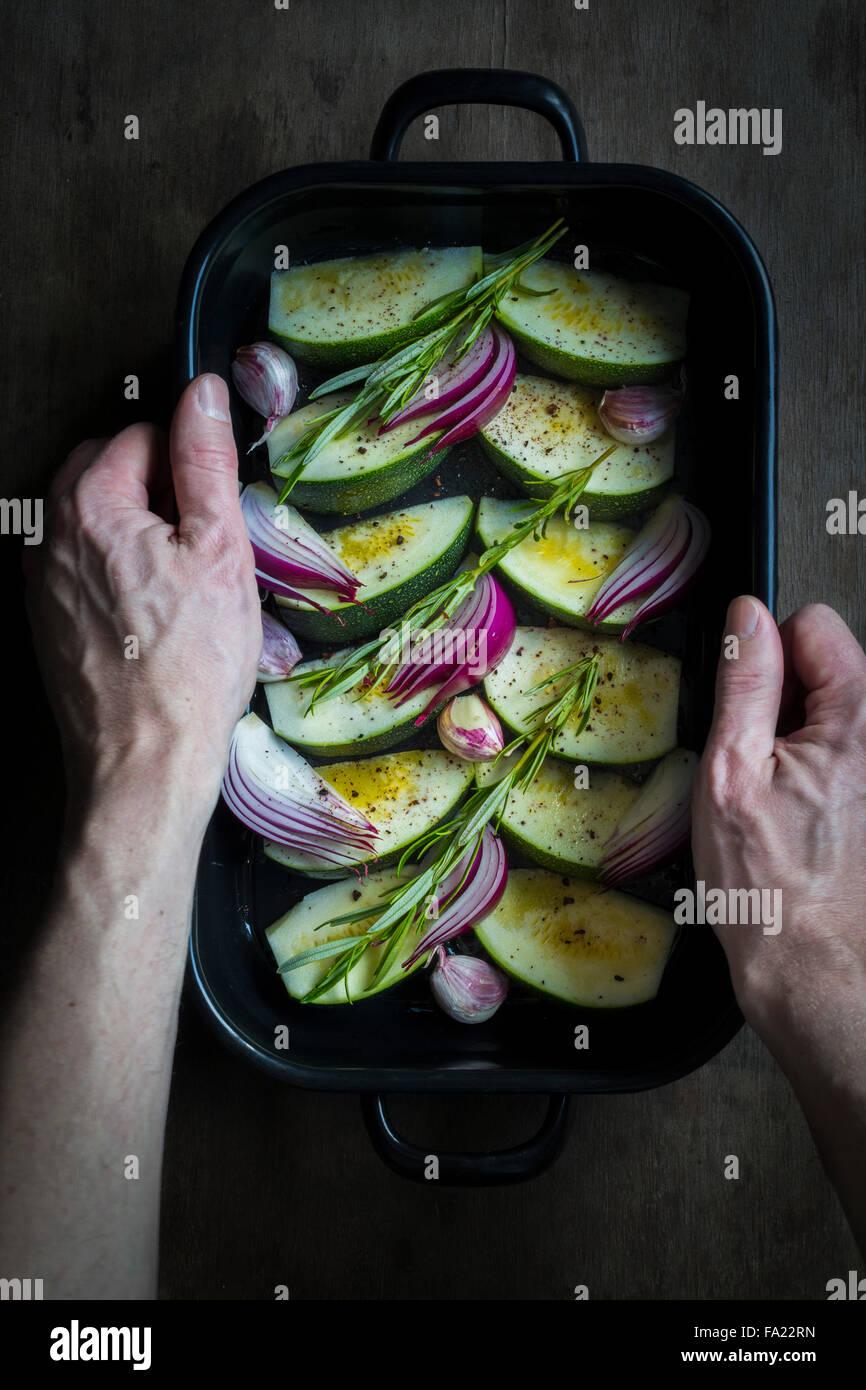 Mani tenendo una teglia da forno con le zucchine, le cipolle e le erbe fresche preparate per la cottura Immagini Stock
