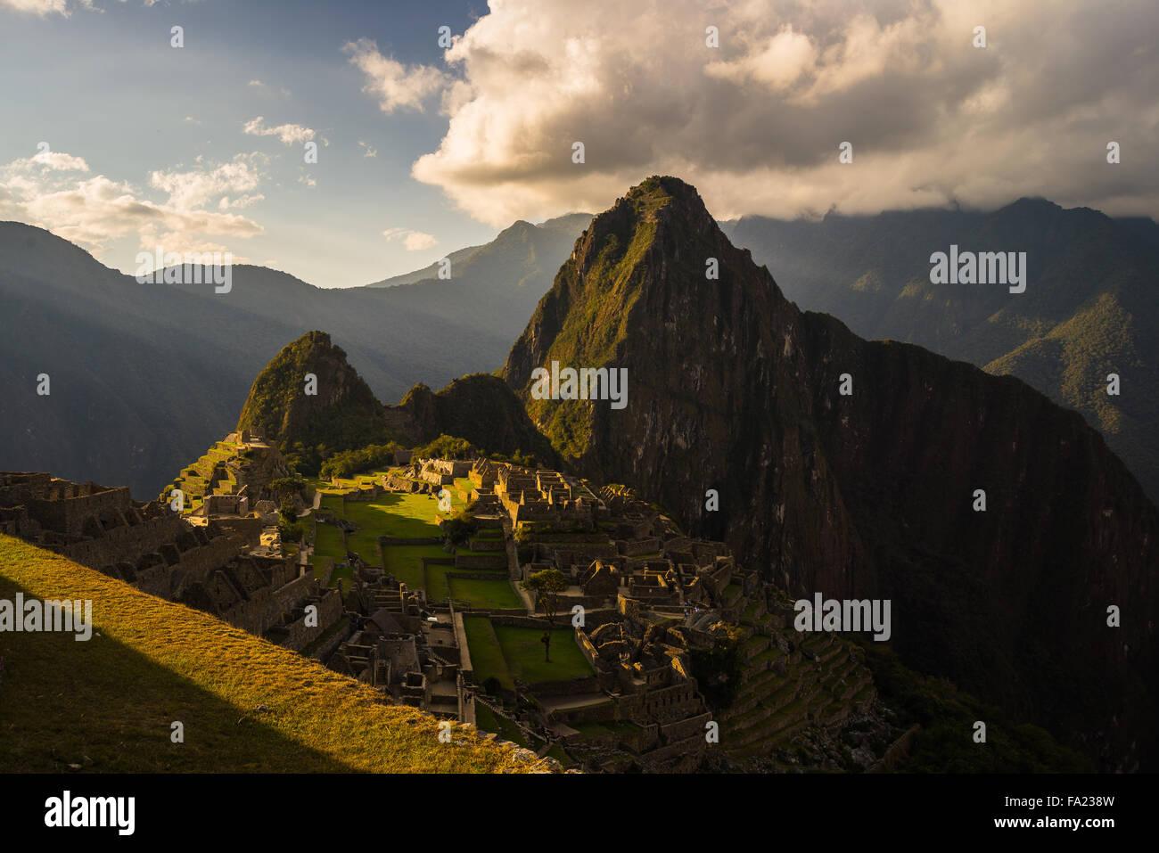 Machu Picchu parzialmente illuminata dall'ultima luce del sole. Ampio angolo di vista dalle terrazze con scenic Immagini Stock