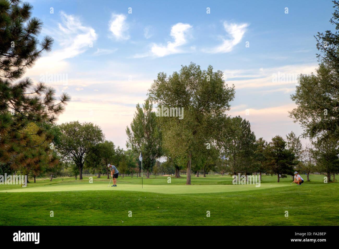Due golfisti giocando su un golf verde. Immagini Stock