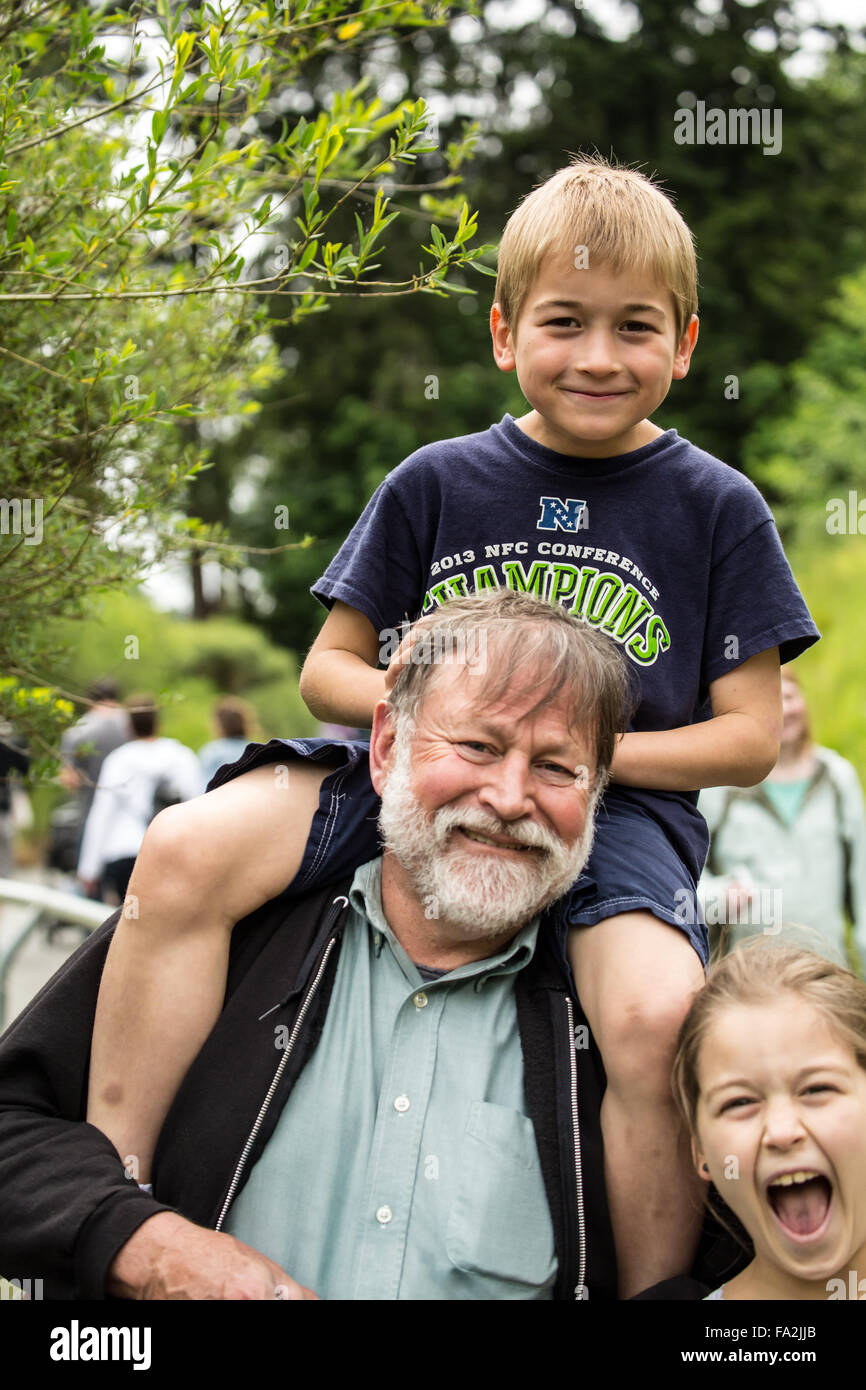 Sette anni di vecchio ragazzo ottenendo un piggyback ride da suo nonno, con i suoi nove anni di suor ottenendo nel Immagini Stock