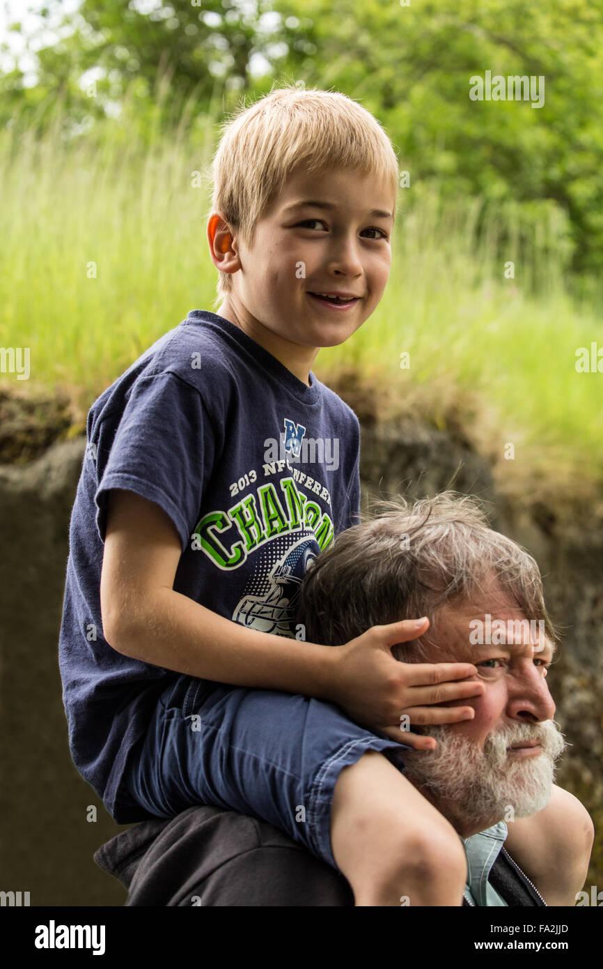 Sette anni di vecchio ragazzo ottenendo un piggyback ride da suo nonno a Seattle, Washington, Stati Uniti d'America Immagini Stock