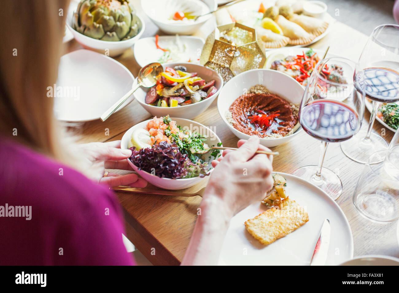 Donna prendendo il cibo nel piatto al ristorante libanese Immagini Stock
