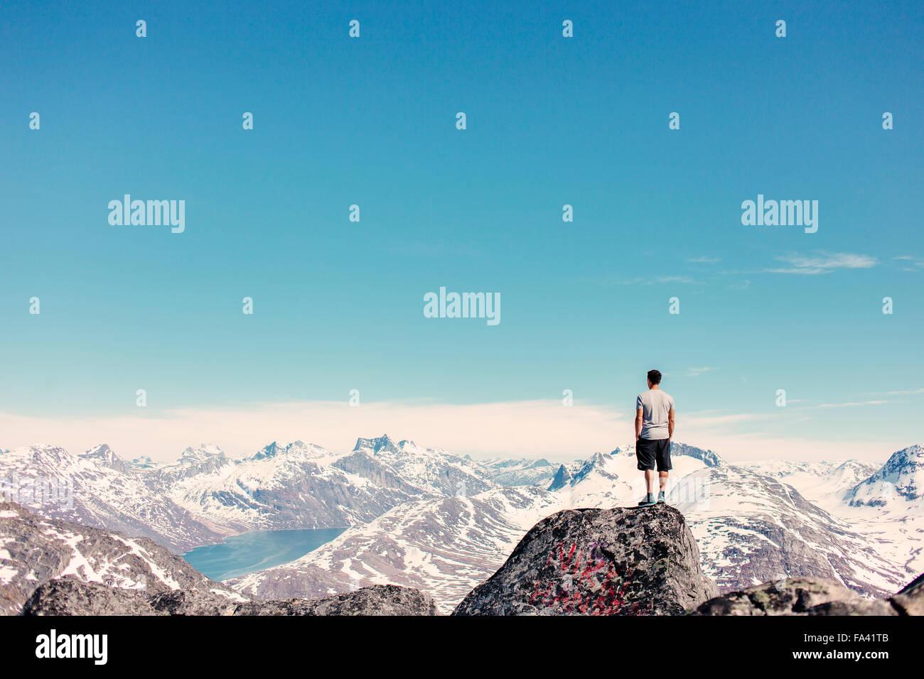 Vista posteriore di uomo in piedi sulla sommità della roccia a guardare montagne coperte di neve Immagini Stock