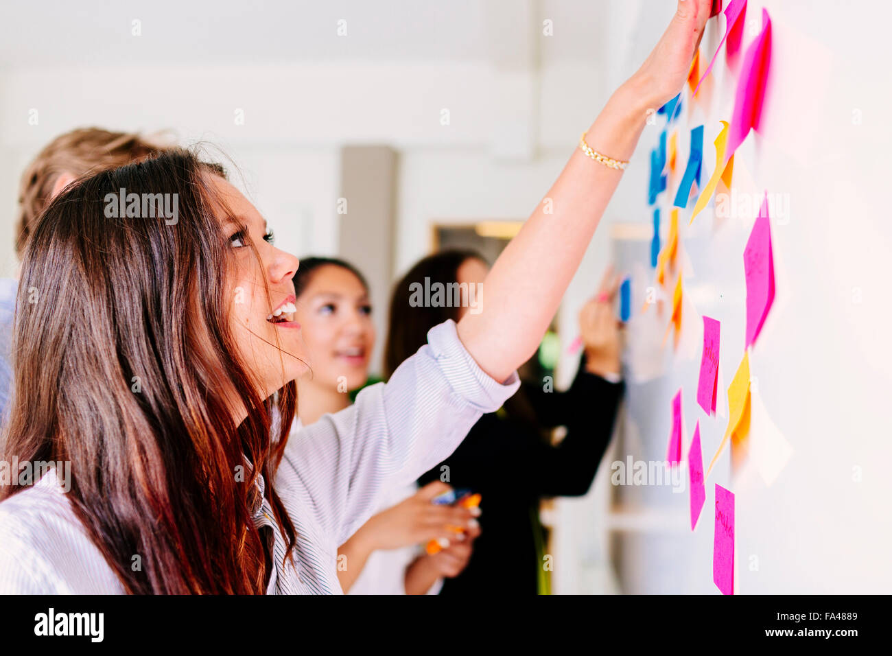 La gente di affari che fissa sticky notes in ufficio Immagini Stock