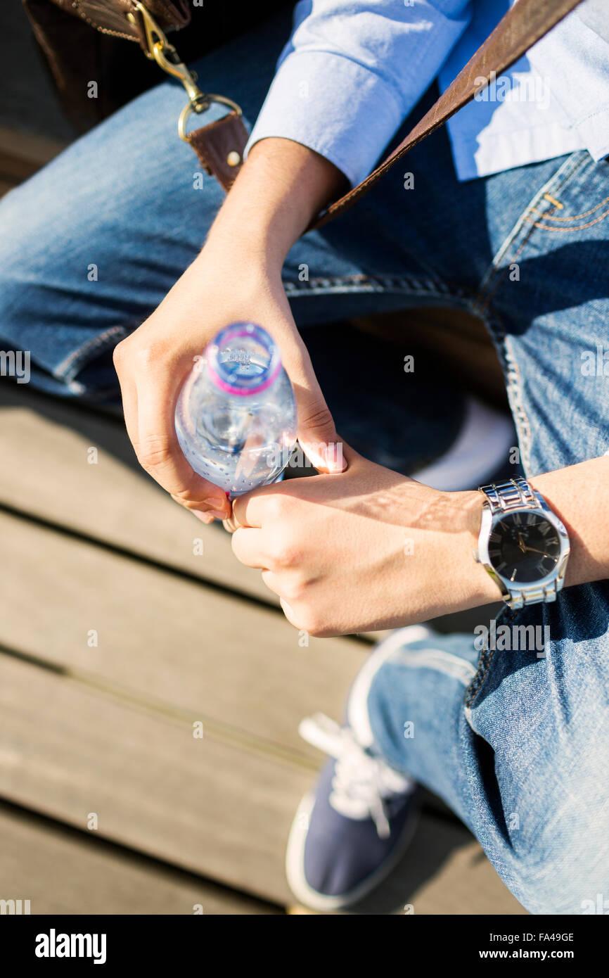 Angolo di Alta Vista del giovane uomo tenendo la bottiglia di acqua all'aperto Immagini Stock