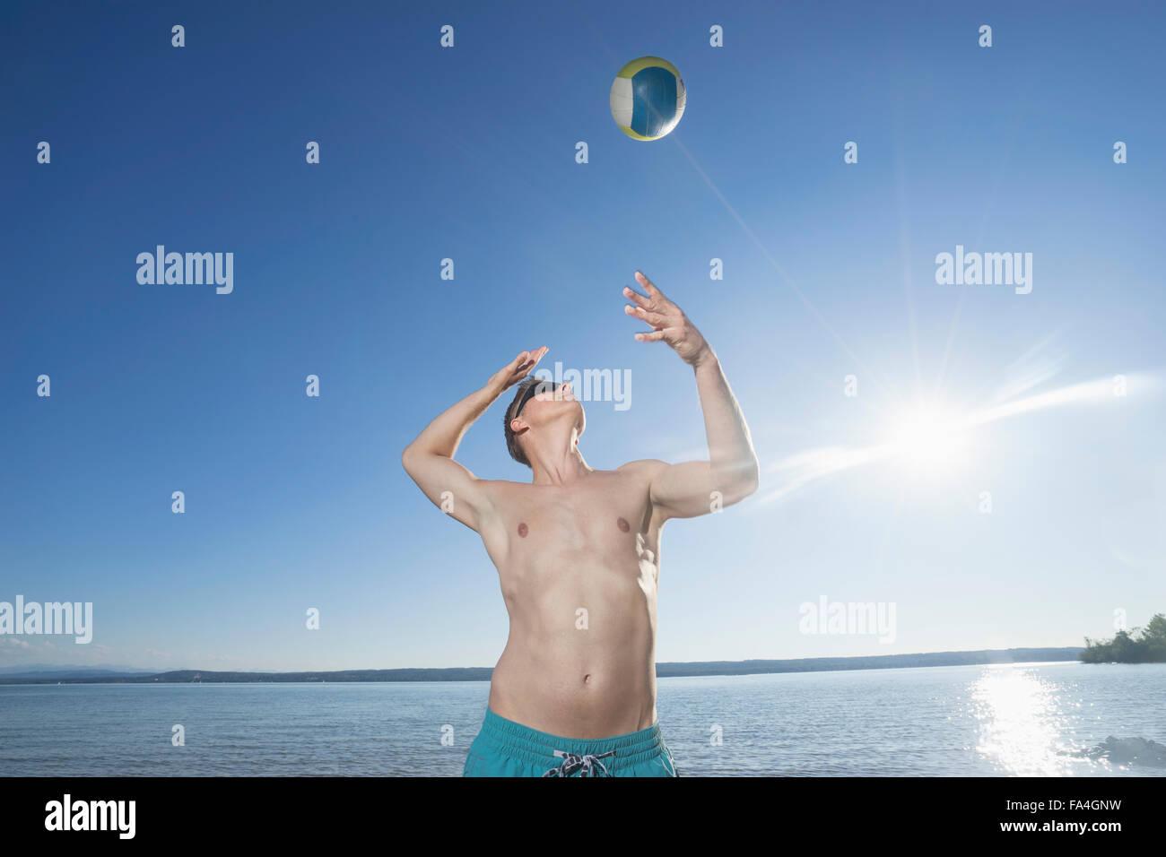 Uomo maturo giocando a pallavolo sul lago, Baviera, Germania Immagini Stock