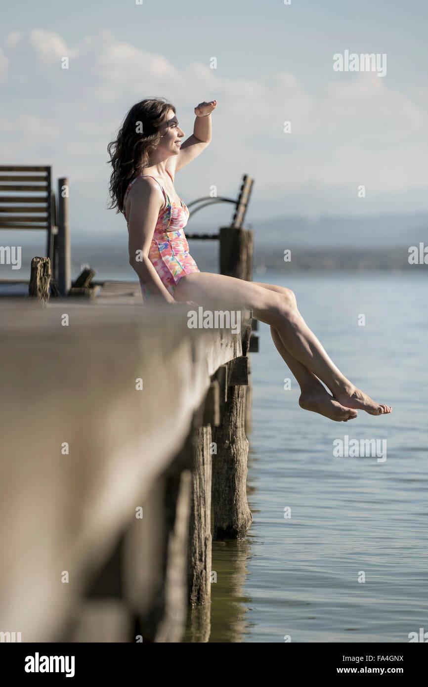 Donna matura seduta in costume da bagno sul molo e guardando a distanza, Baviera, Germania Immagini Stock