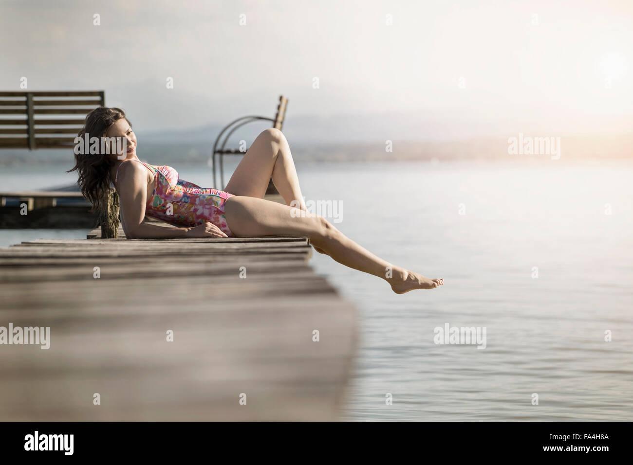 Donna matura giacente in costume da bagno sul molo, Baviera, Germania Immagini Stock