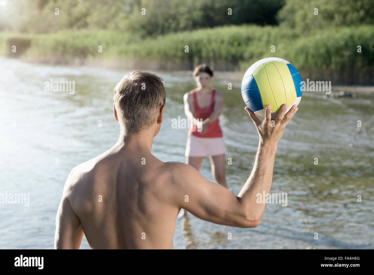 Coppia matura giocando a pallavolo al lago, Baviera, Germania Immagini Stock