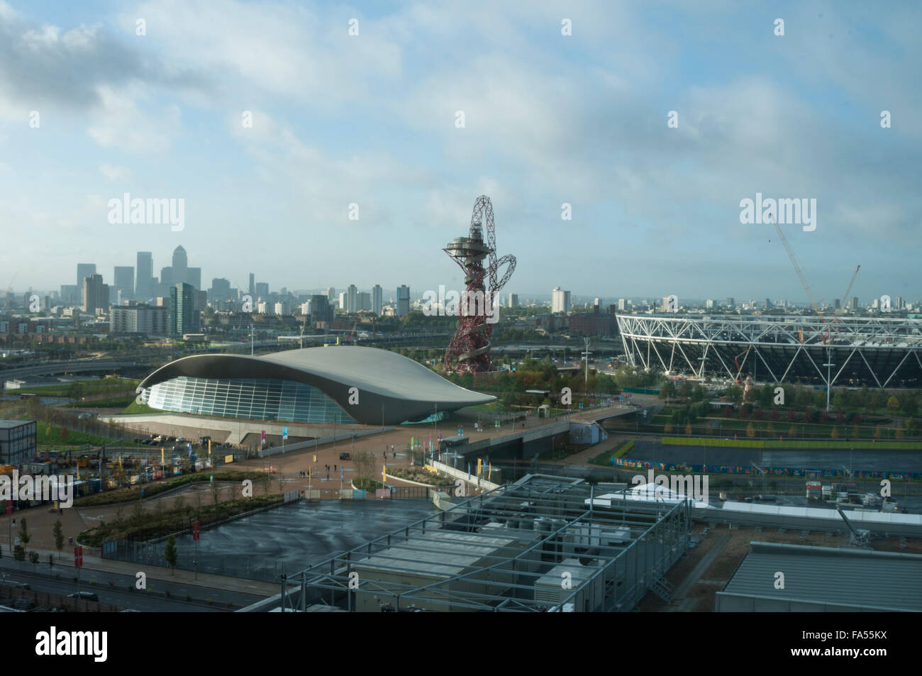 La mattina presto vista del London Aquatics Centre dell'architetto Zaha Hadid con Canary Wharf in background. Immagini Stock