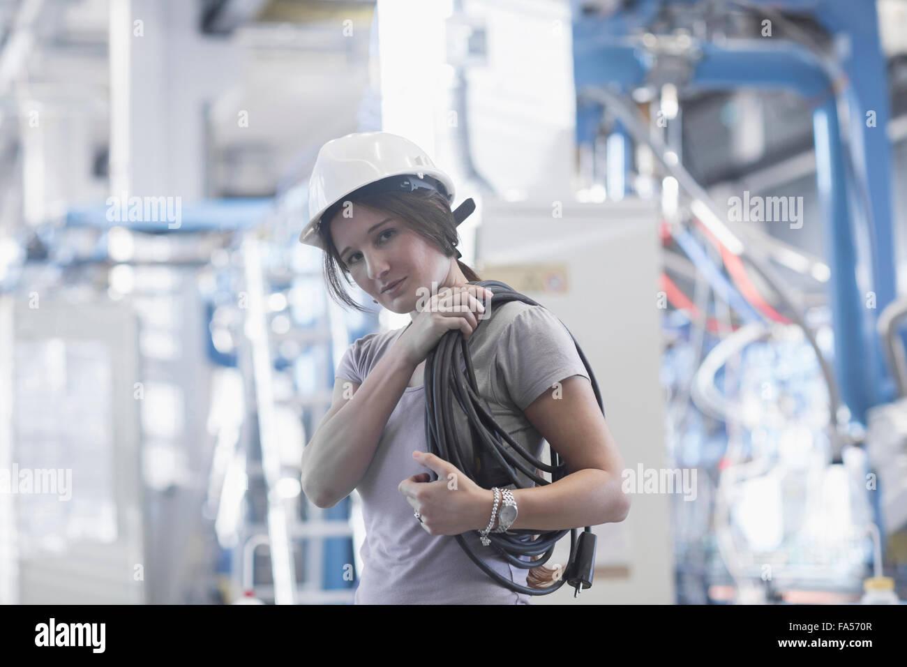 Tecnico femminile che porta la bobina di corda sulla spalla in un impianto industriale di Freiburg im Breisgau, Immagini Stock