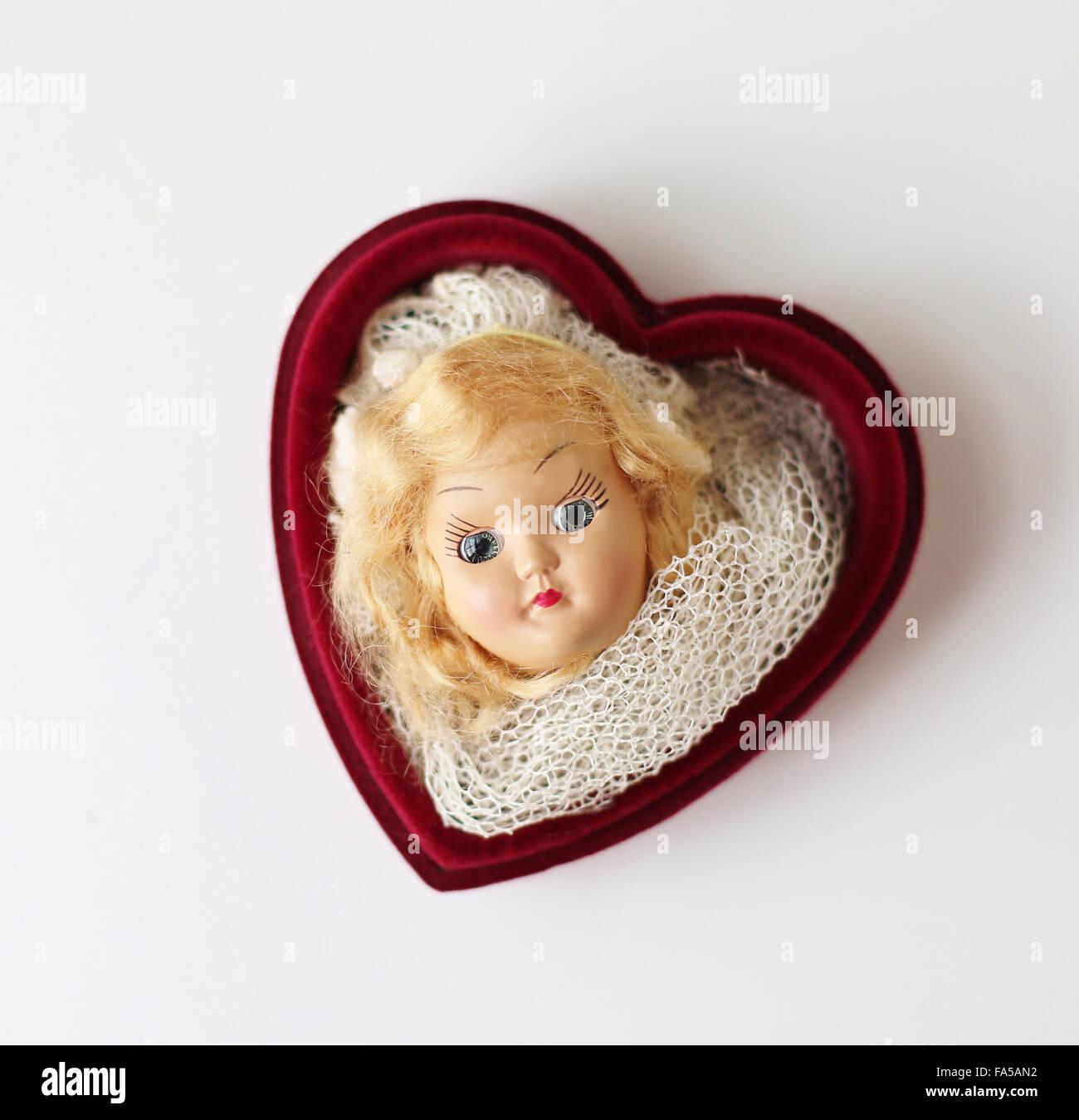 Un vecchio testa di bambola di una donna in un cuore scatola sagomata. Immagini Stock