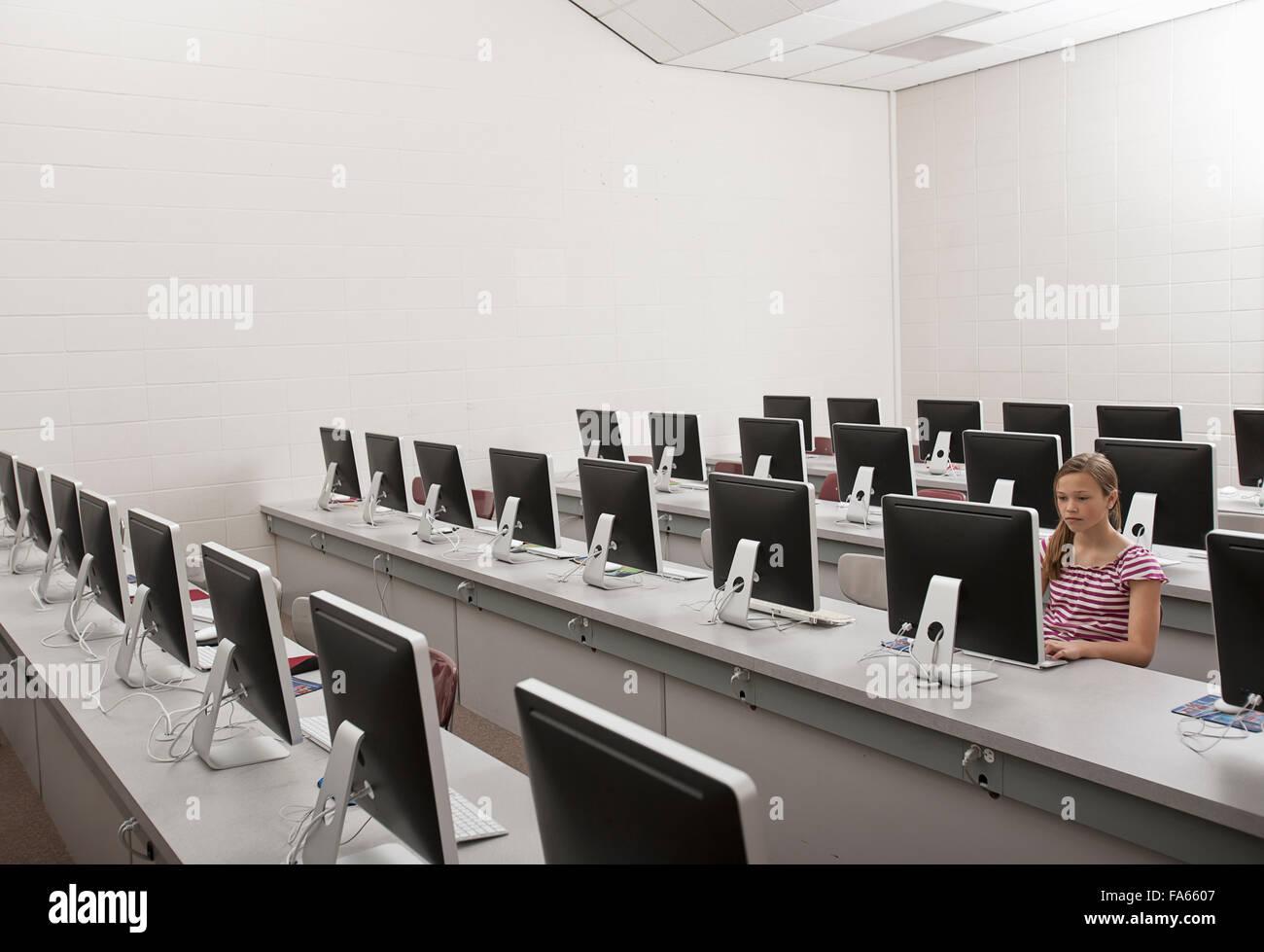 Una scuola camera, un laboratorio informatico con righe di schermi e posti a sedere. Una persona giovane seduto Immagini Stock