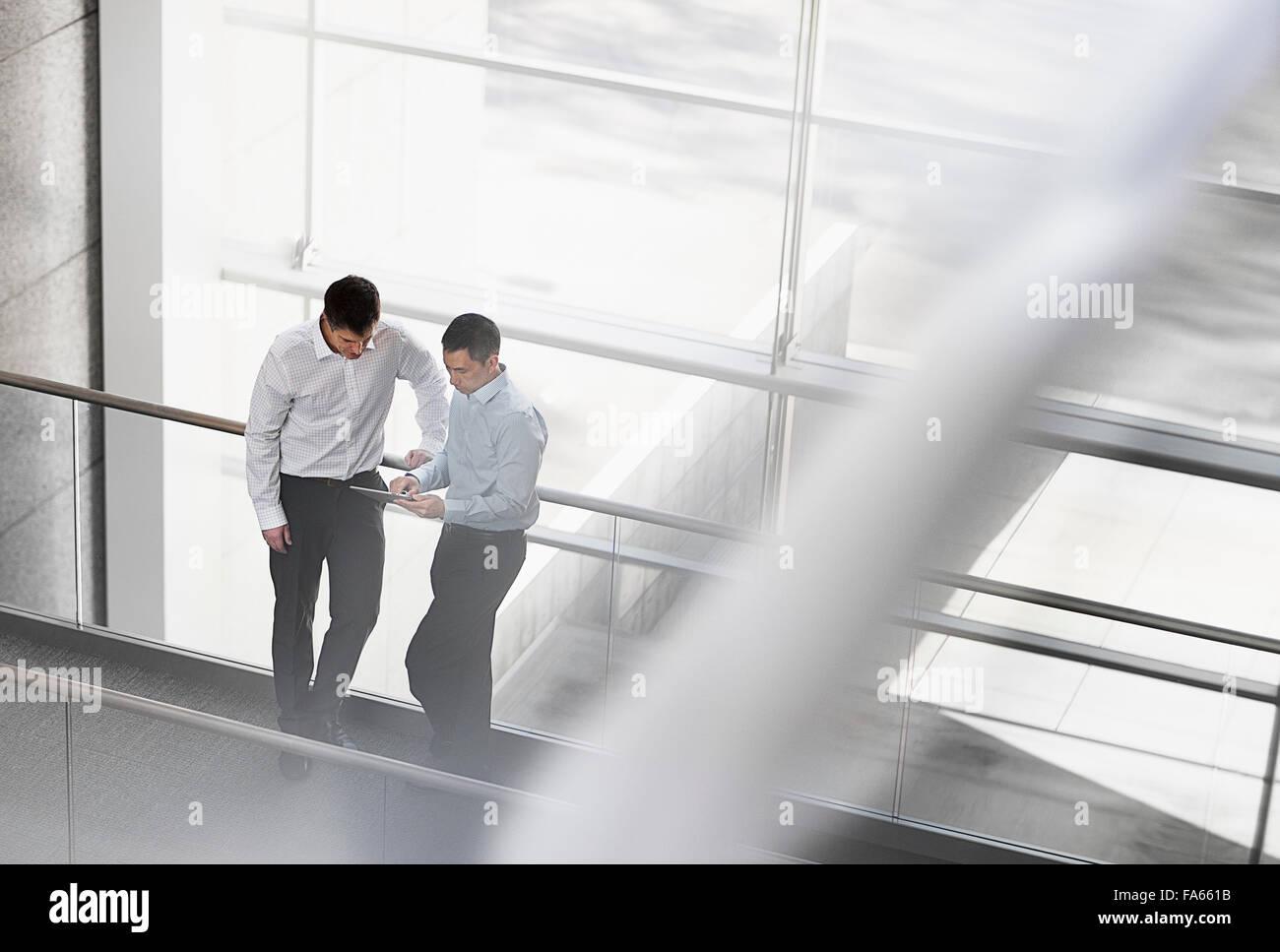 Due uomini stavano in piedi dalle grandi finestre di un edificio, guardando lo schermo di una tavoletta digitale. Immagini Stock