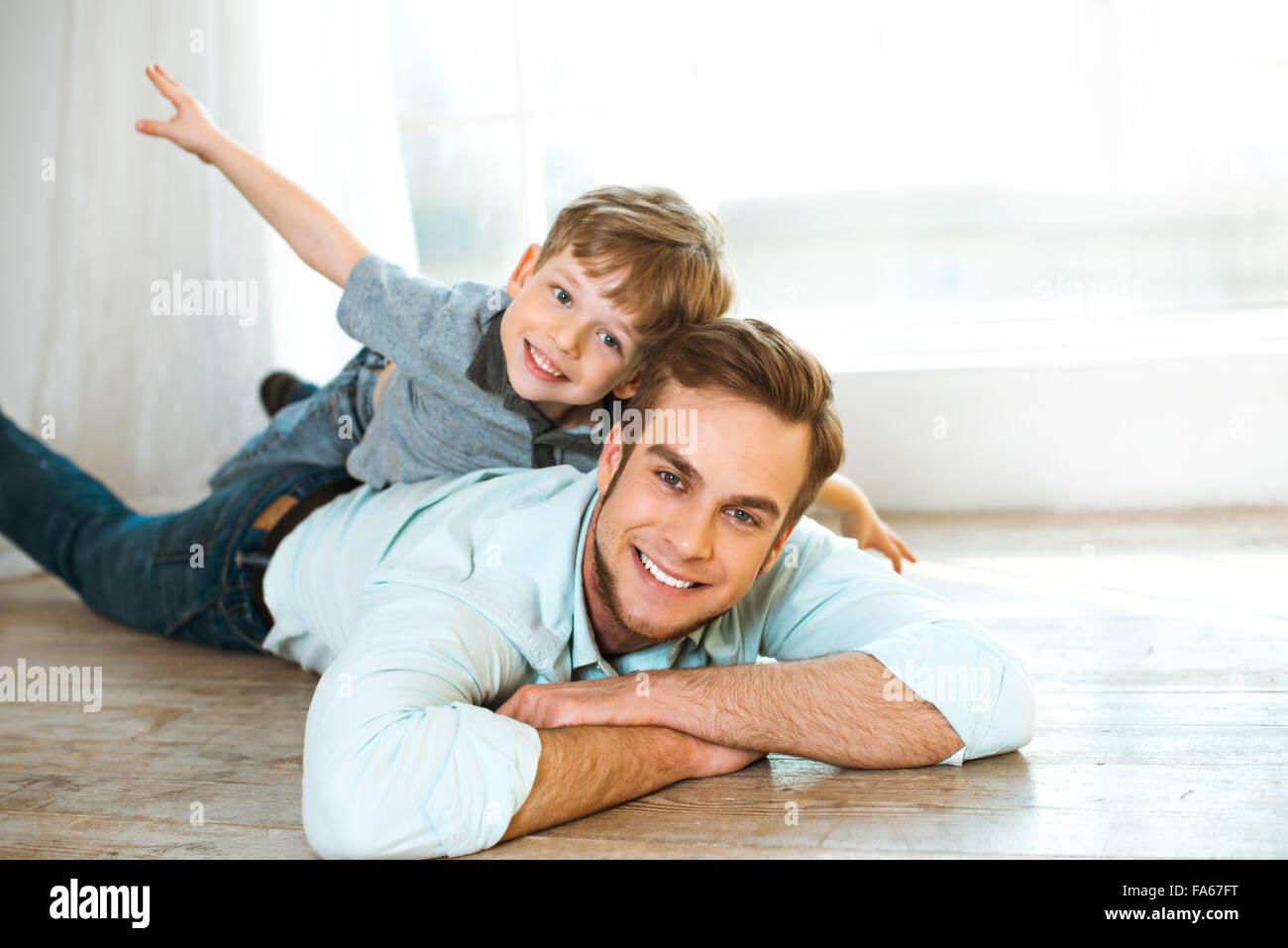Little Boy e suo padre sul pavimento in legno Immagini Stock