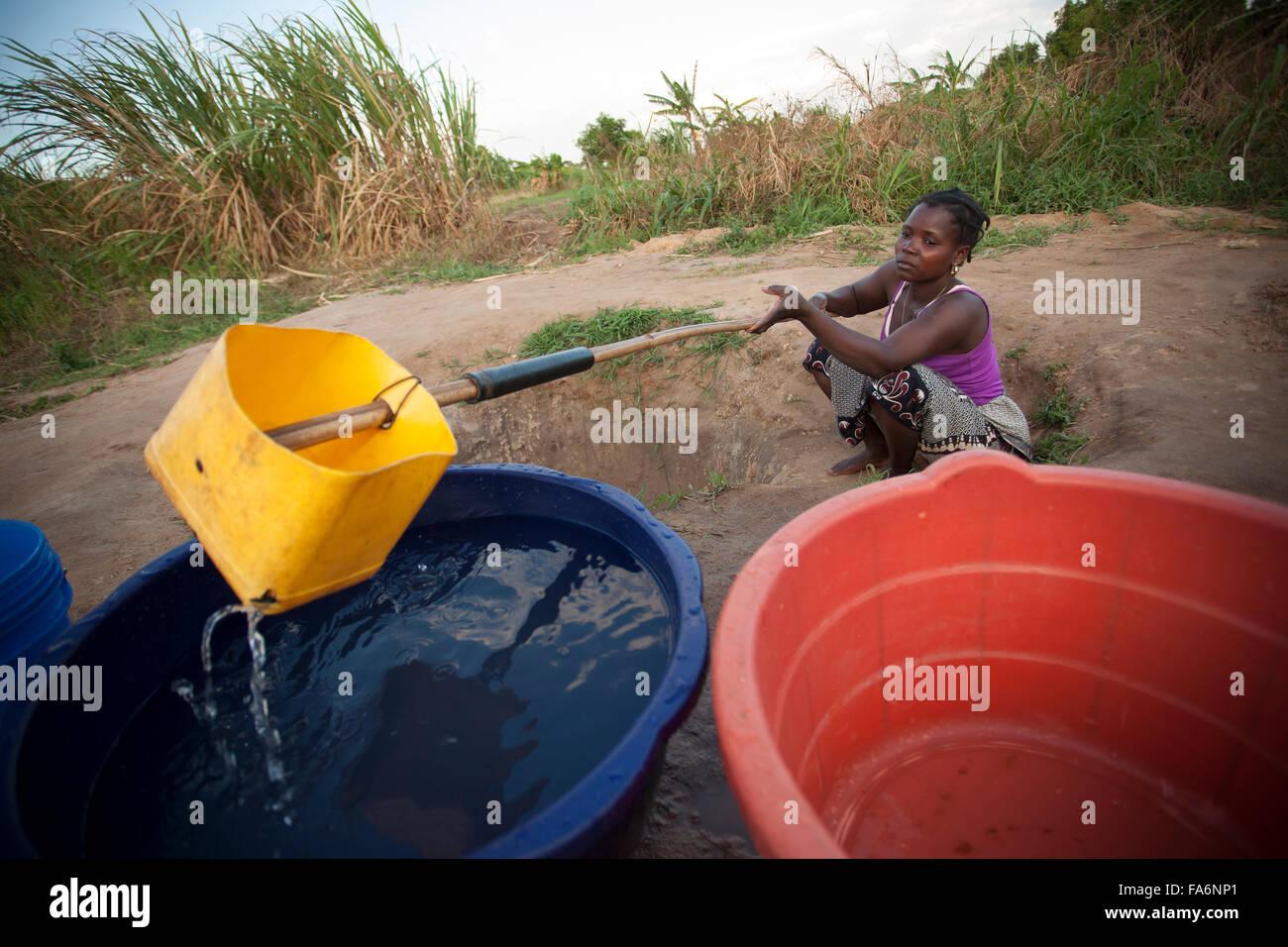 Residenti attingere acqua fangosa da mano-scavò fonti a Nampula, Mozambico. Immagini Stock