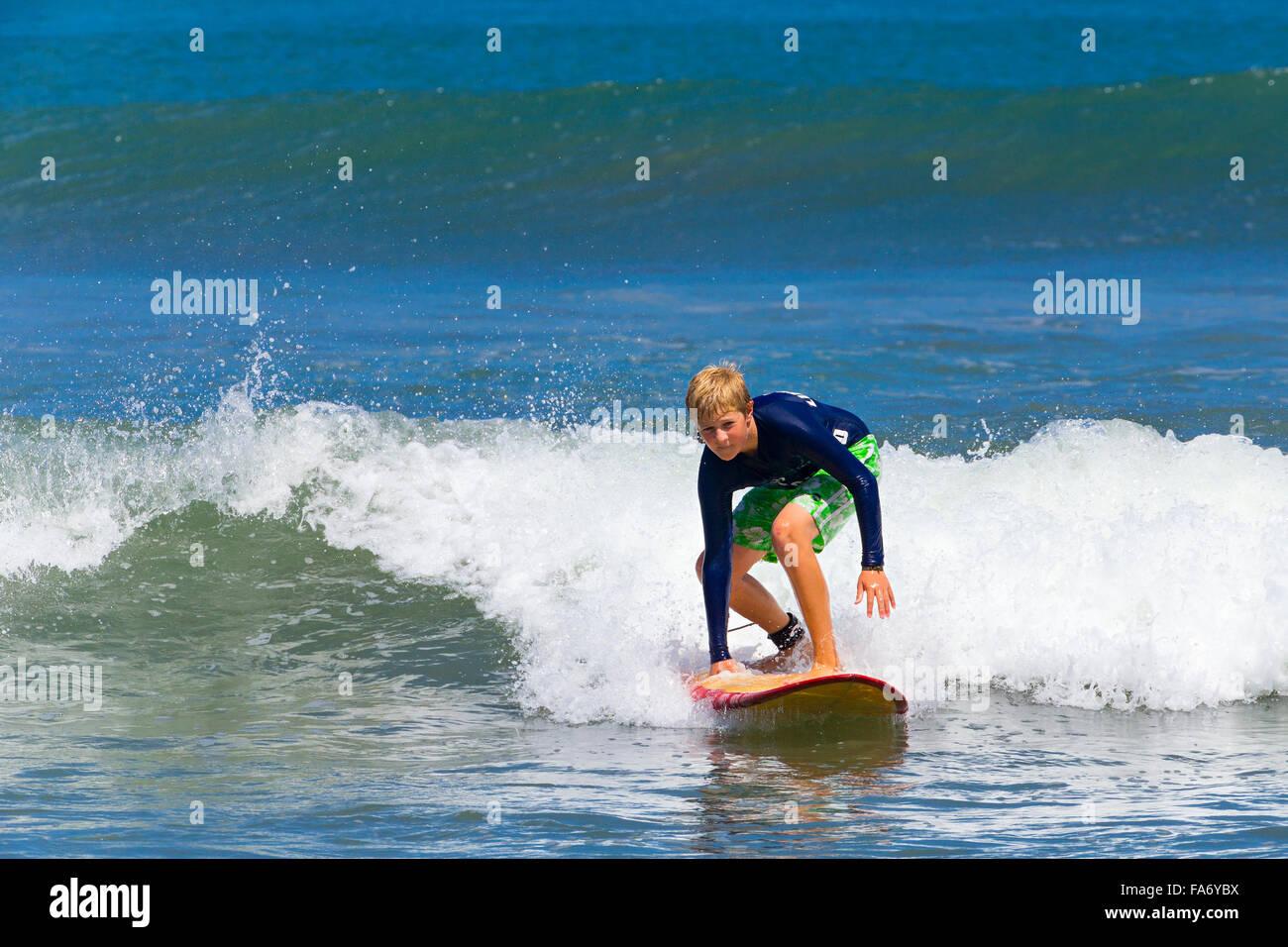 Un ragazzo, 12 anni, surf, Kuta, Legian beach e surf paradise, Bali, Indonesia Immagini Stock