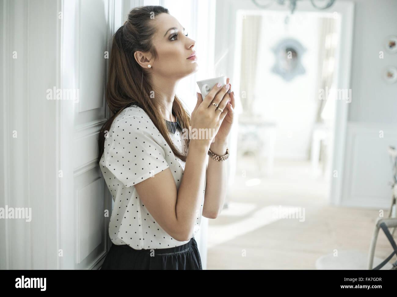 Giovane donna elegante bere un caffè scuro Immagini Stock