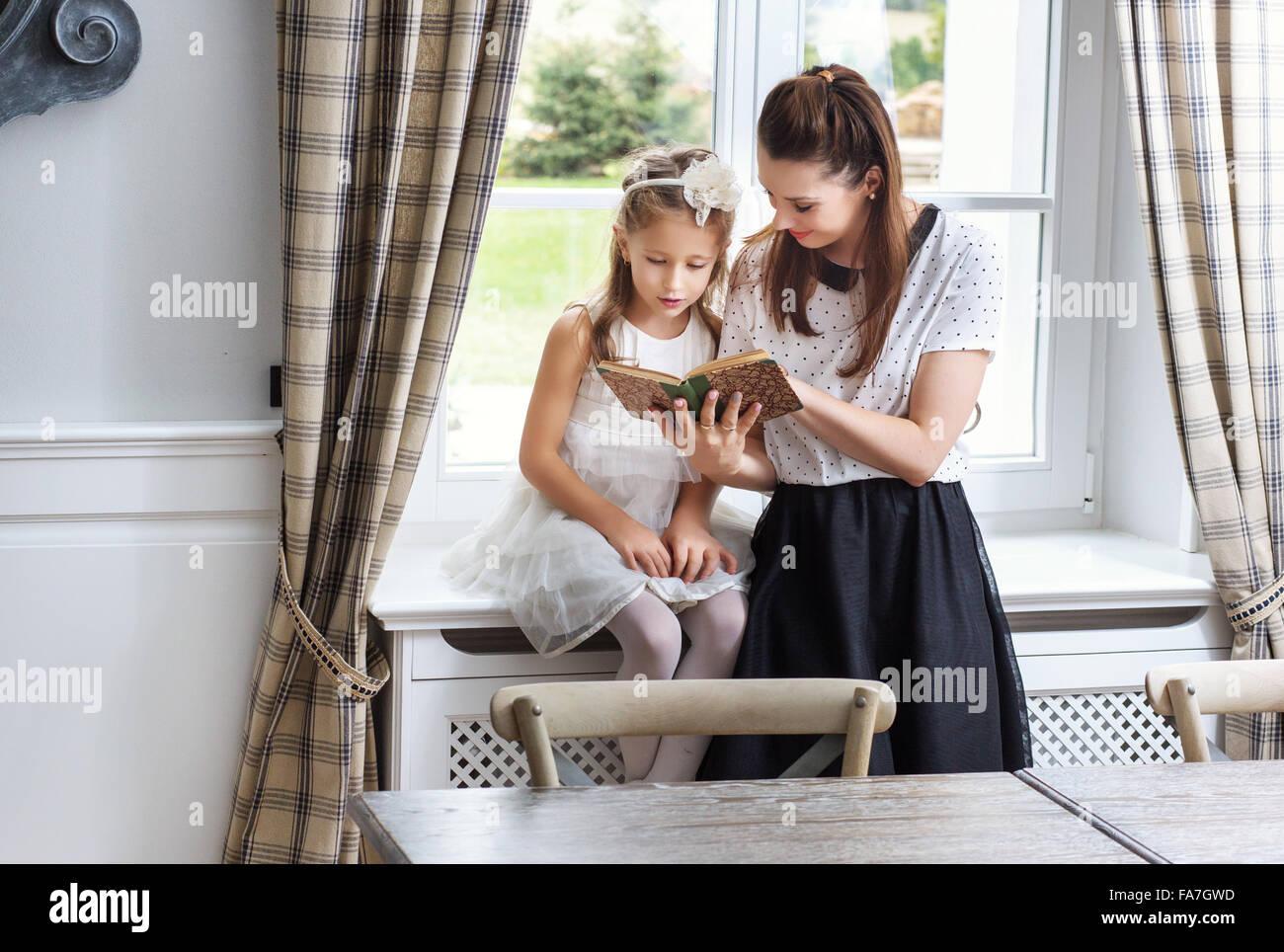 Madre premurosa insegnamento carino figlia come leggere Immagini Stock
