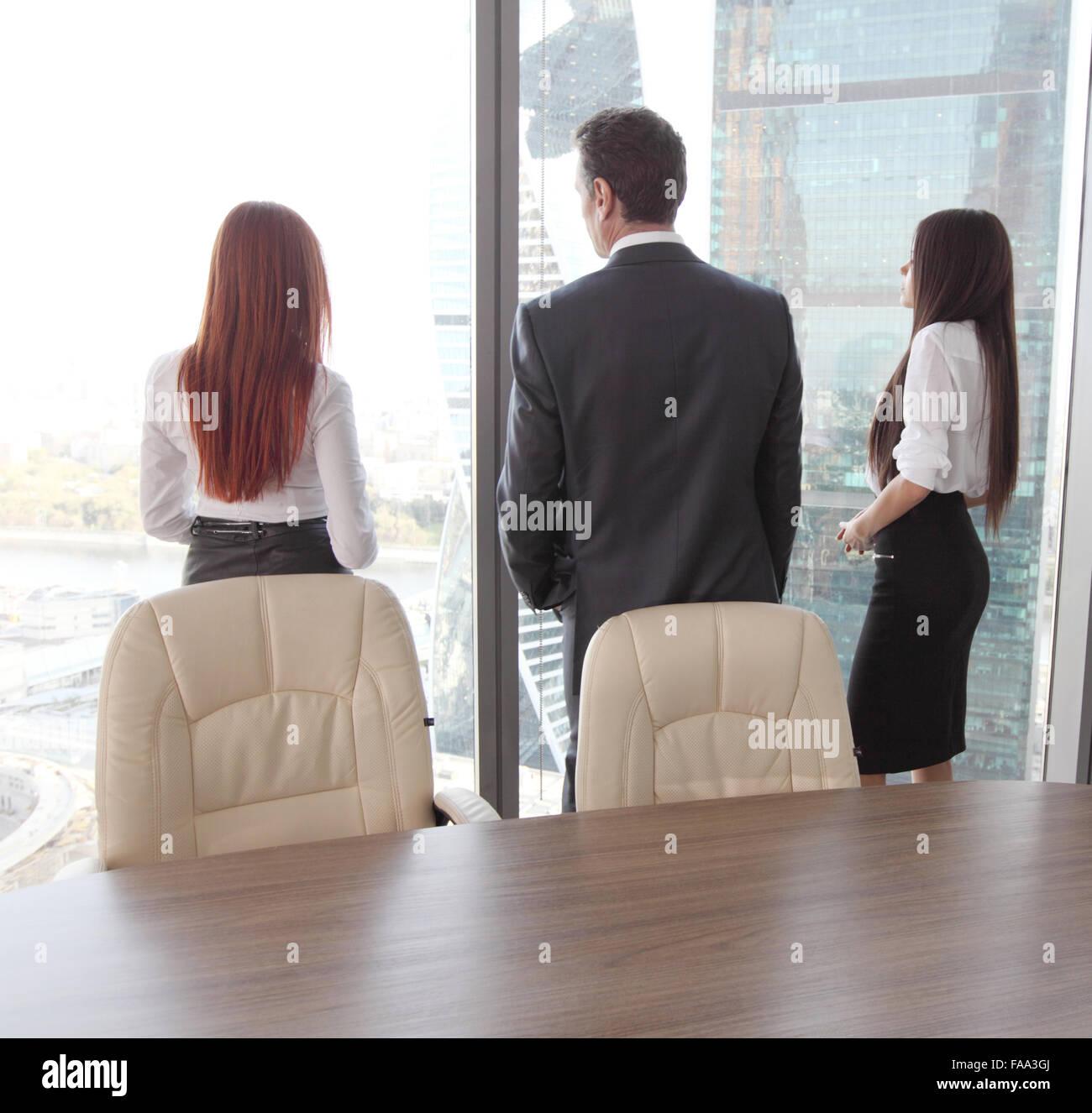 Vista posteriore della gente di affari cercando in corrispondenza della finestra Immagini Stock