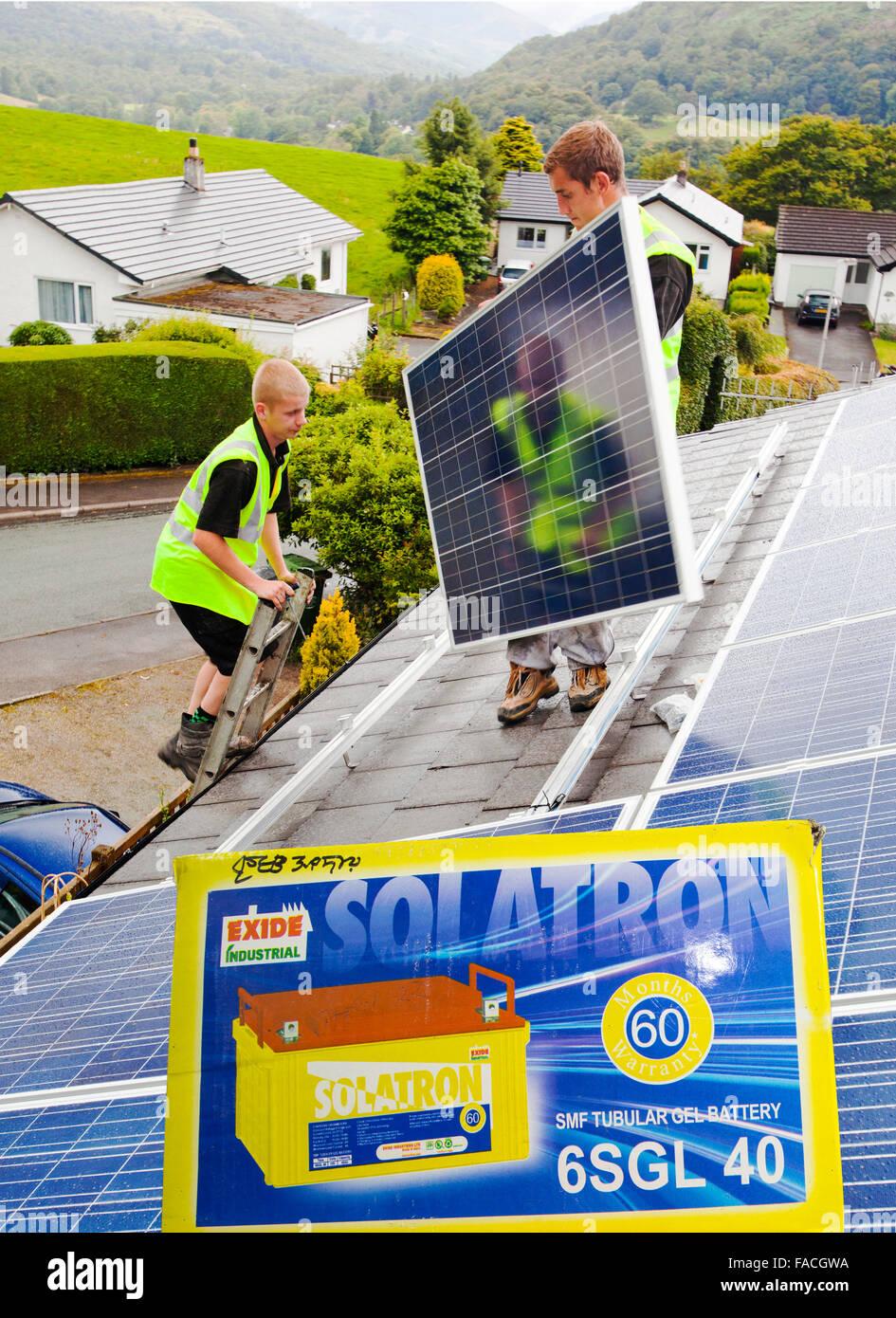 I tecnici di montaggio foto solare fotovoltaica in pannelli per la mia casa tetto in Ambleside, Cumbria. Sebbene Immagini Stock