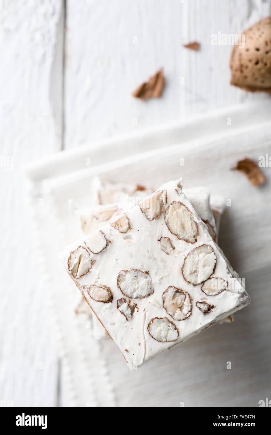 Fette di torrone bianco con mandorle, un tradizionale italiano Dolce di Natale Immagini Stock