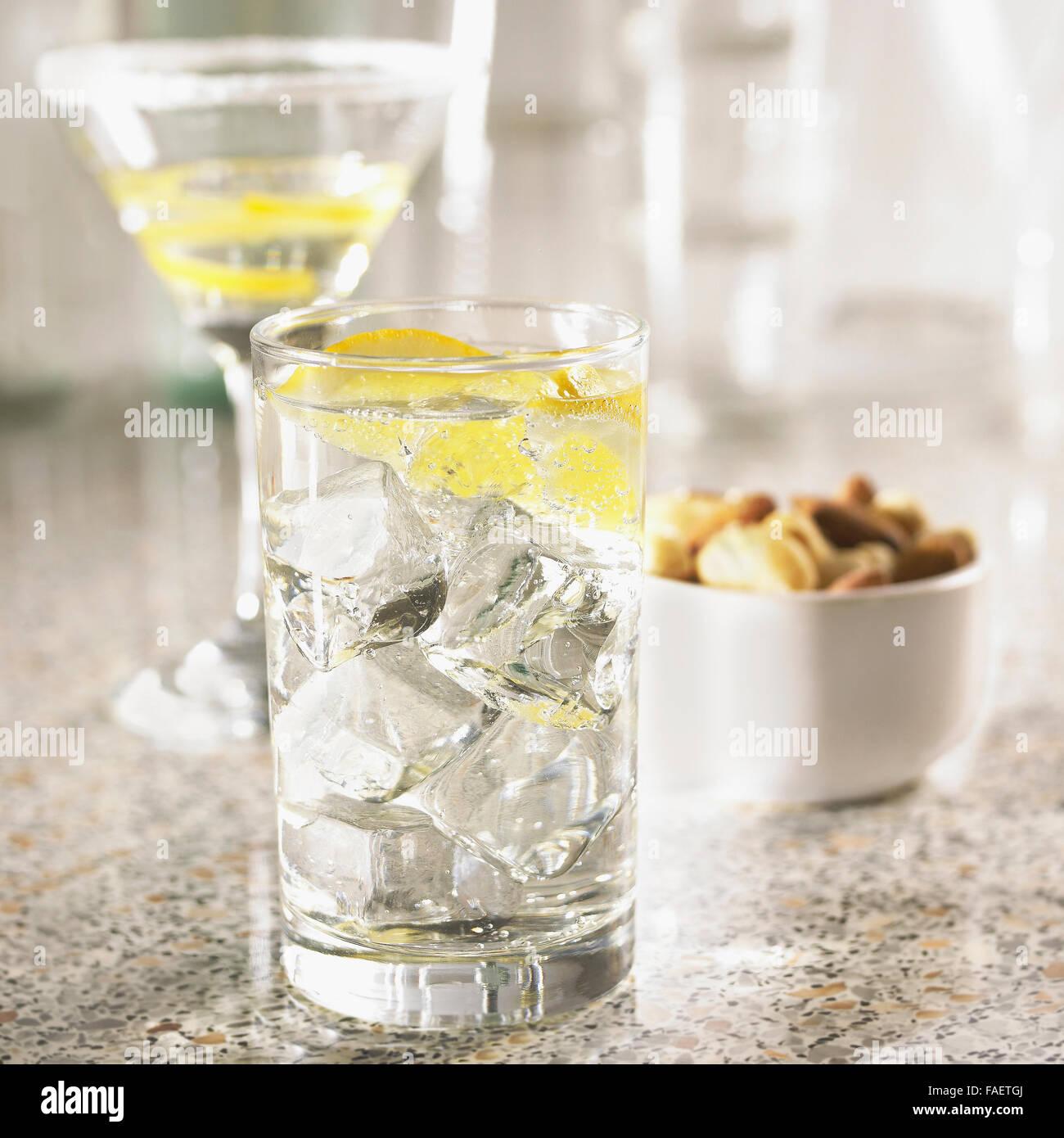 Bicchiere di gin tonic su un banco di bar con cocktail di vuoto bicchieri e noci di acagiù fuori fuoco dietro. Immagini Stock