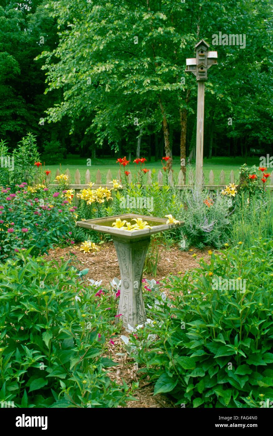 Fantasiosa bird garden con bagno di uccelli e gigli galleggianti in acqua. Costruiti a mano case di uccelli surrouneded Immagini Stock