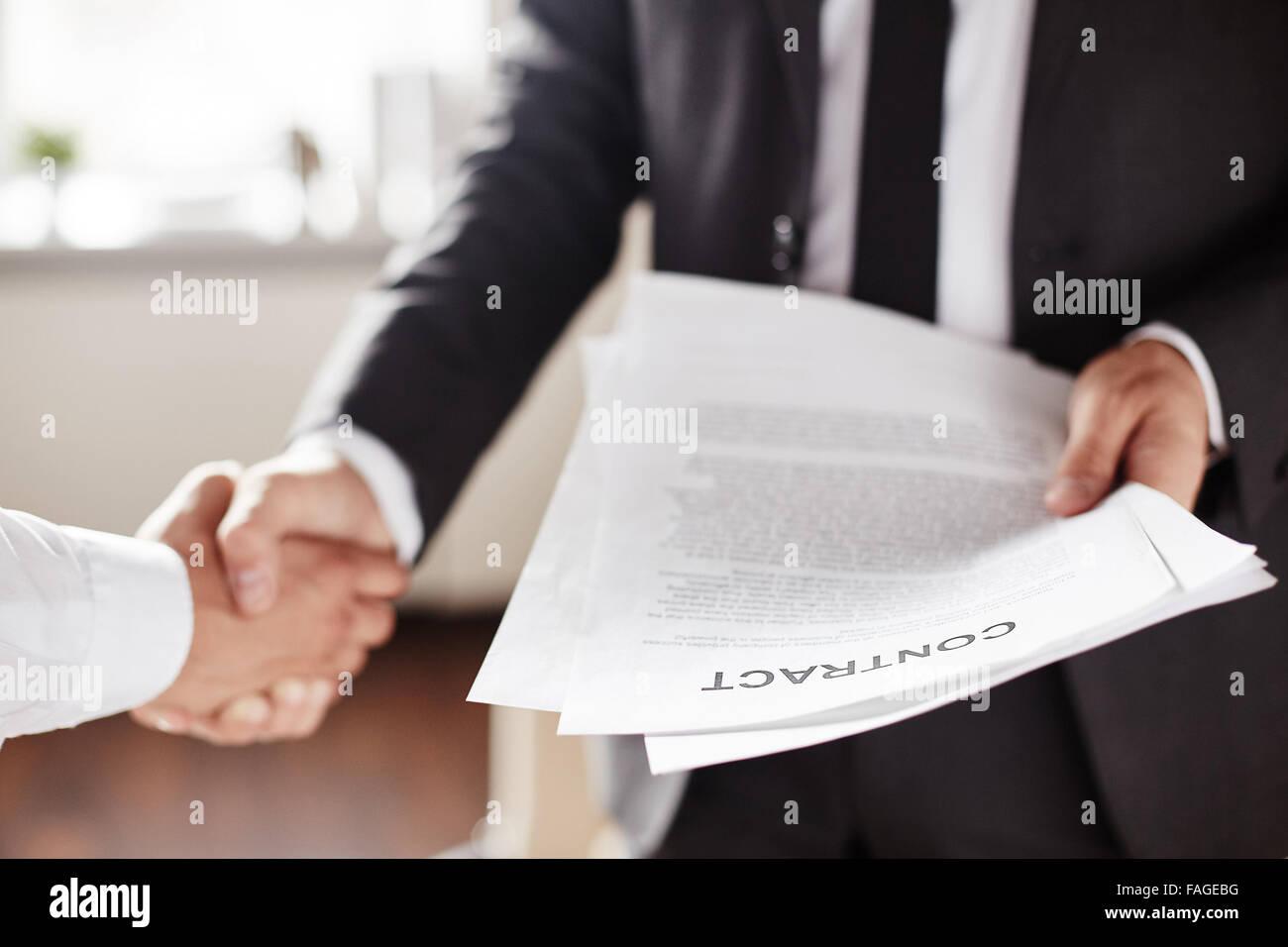 Contratto di Business tenuto da parte dell'imprenditore durante l'handshake con il partner Immagini Stock