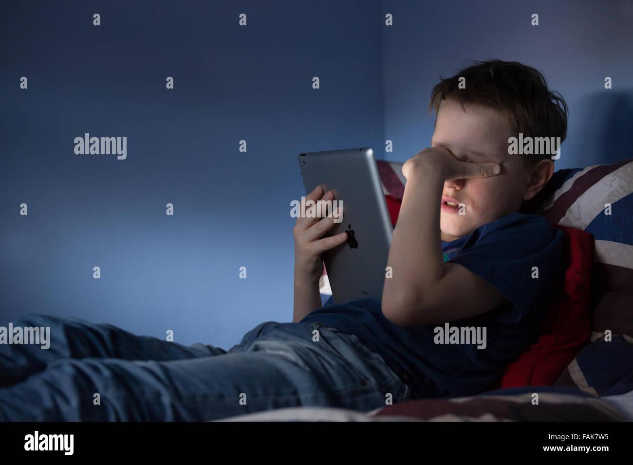 Online cyber bullismo Bullismo foto di un ragazzo sconvolto nella sua camera da letto guardando doloroso messaggi Immagini Stock