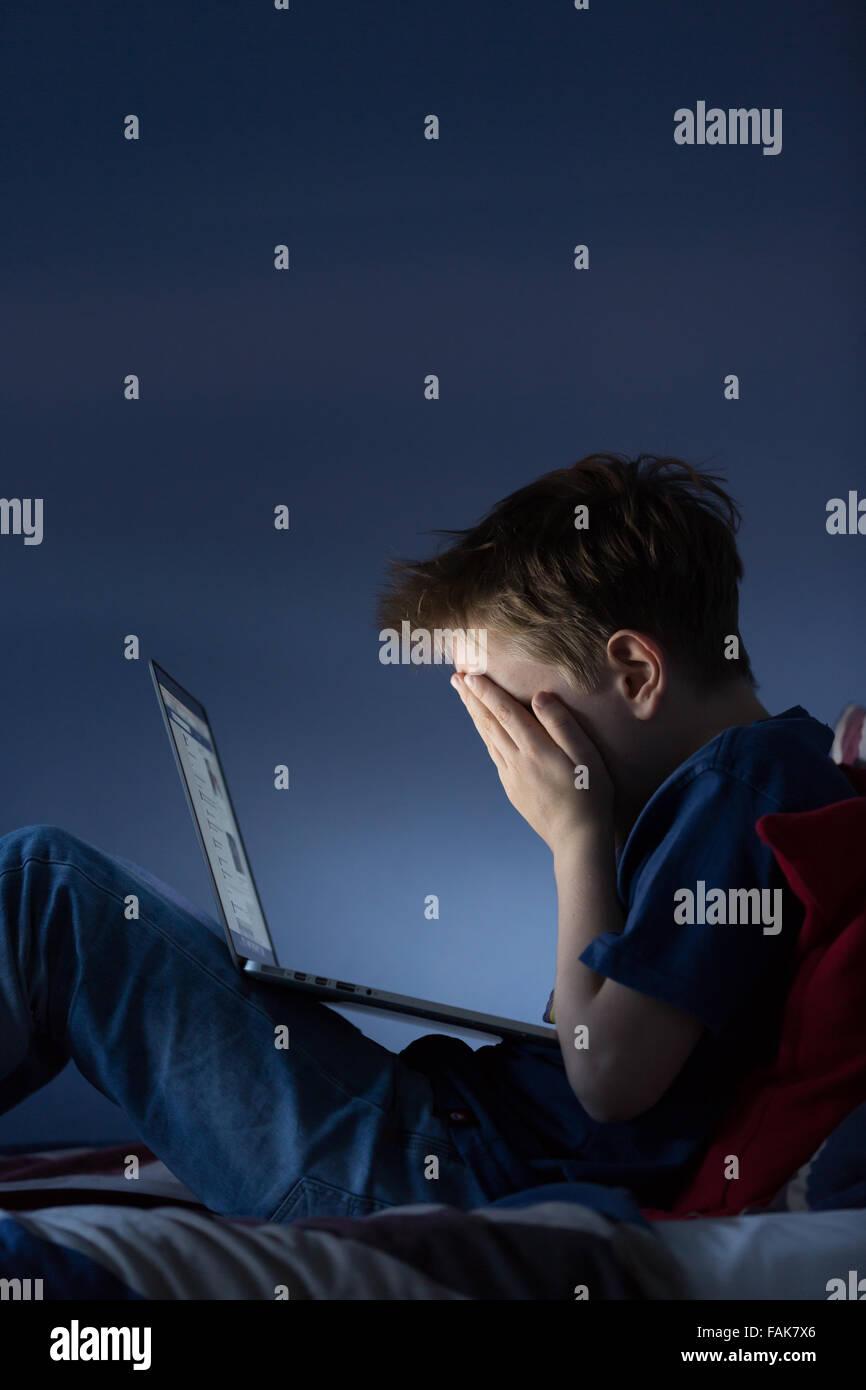 Online cyber bullismo Bullismo foto di un ragazzo sconvolto nella sua camera da letto guardando i messaggi sui social Immagini Stock