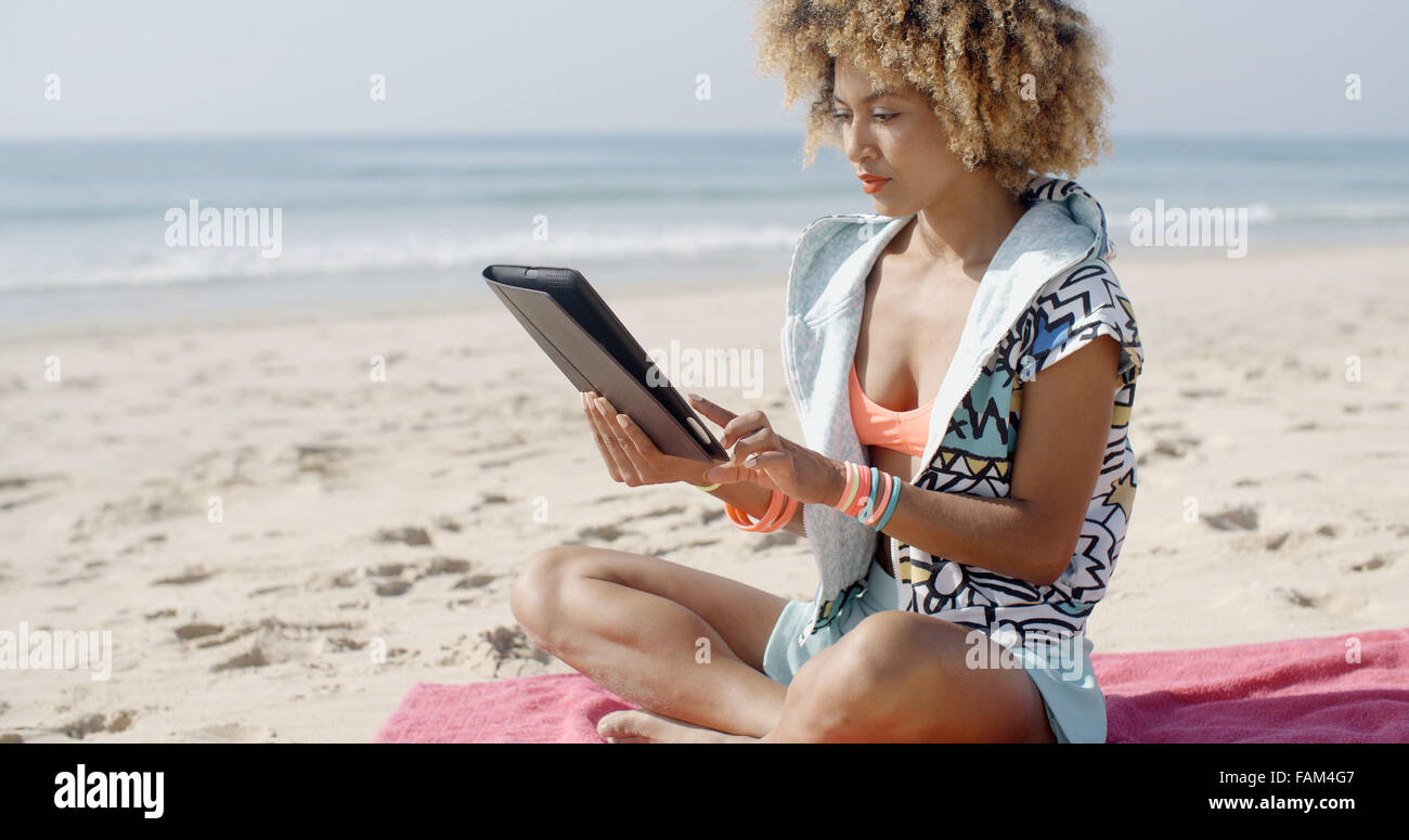 La donna utilizza il Touchpad Tablet sulla spiaggia Immagini Stock