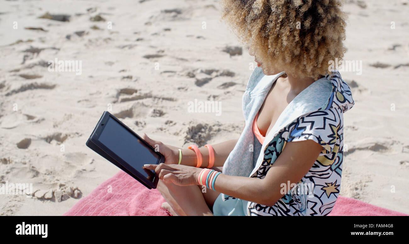 Donna usa Tablet sulla spiaggia Immagini Stock