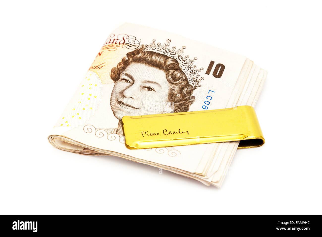 Clip di denaro contante oro valuta Pierre Cardin UK dieci libbre di esclusione porta tagliare lo sfondo bianco isolato Immagini Stock