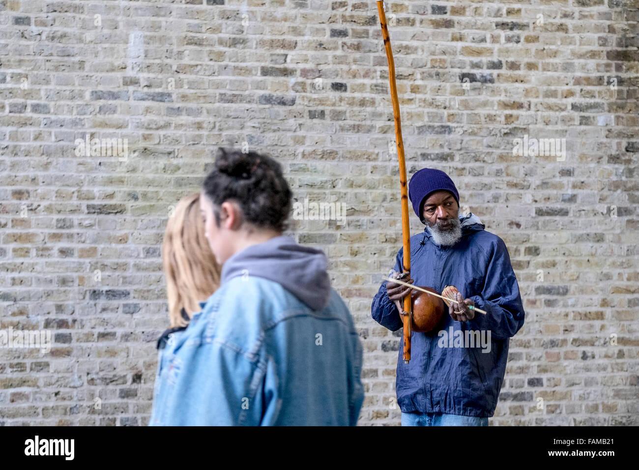 Sulla South Bank di Londra un busker, Rabimsha svolge un berimbau, un tradizionale africana/strumento brasiliano. Immagini Stock
