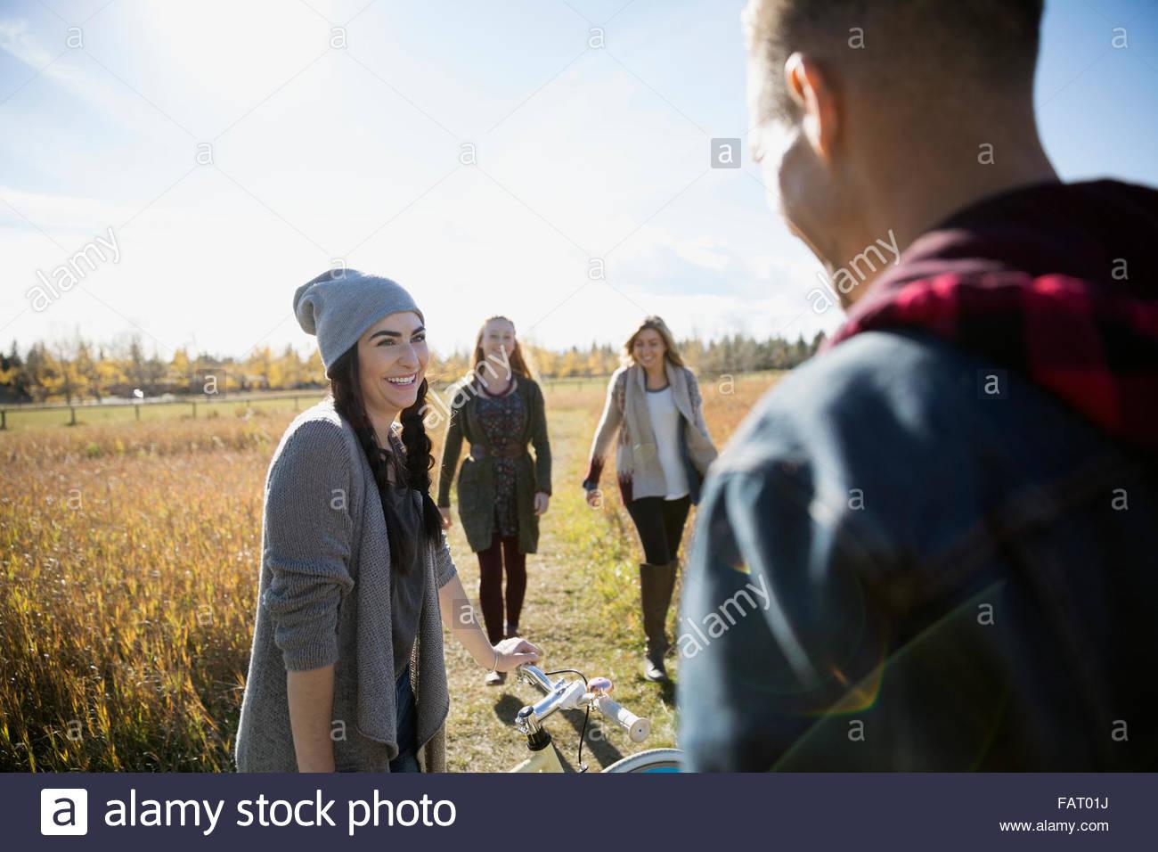 Amici con passeggiate in bicicletta nel soleggiato Campo di autunno Immagini Stock