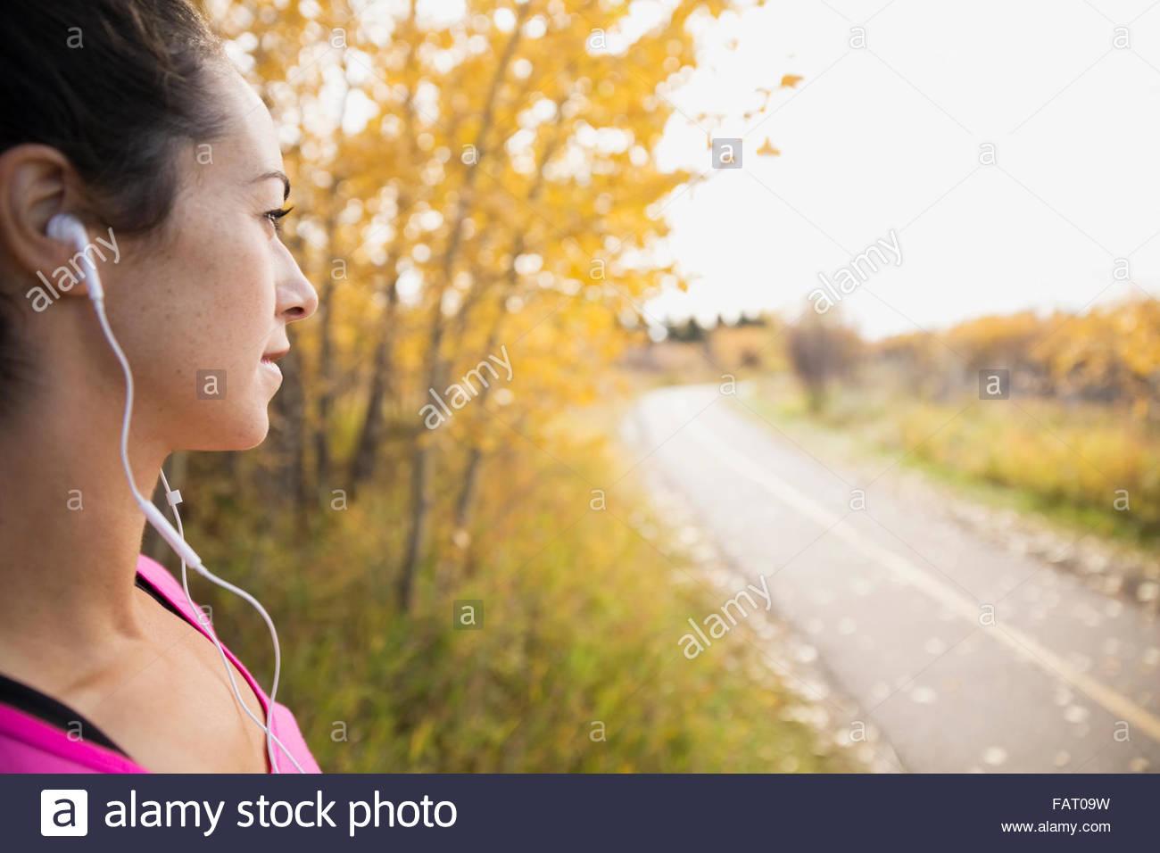 Pareggiatore con cuffie guardando al percorso di autunno Immagini Stock