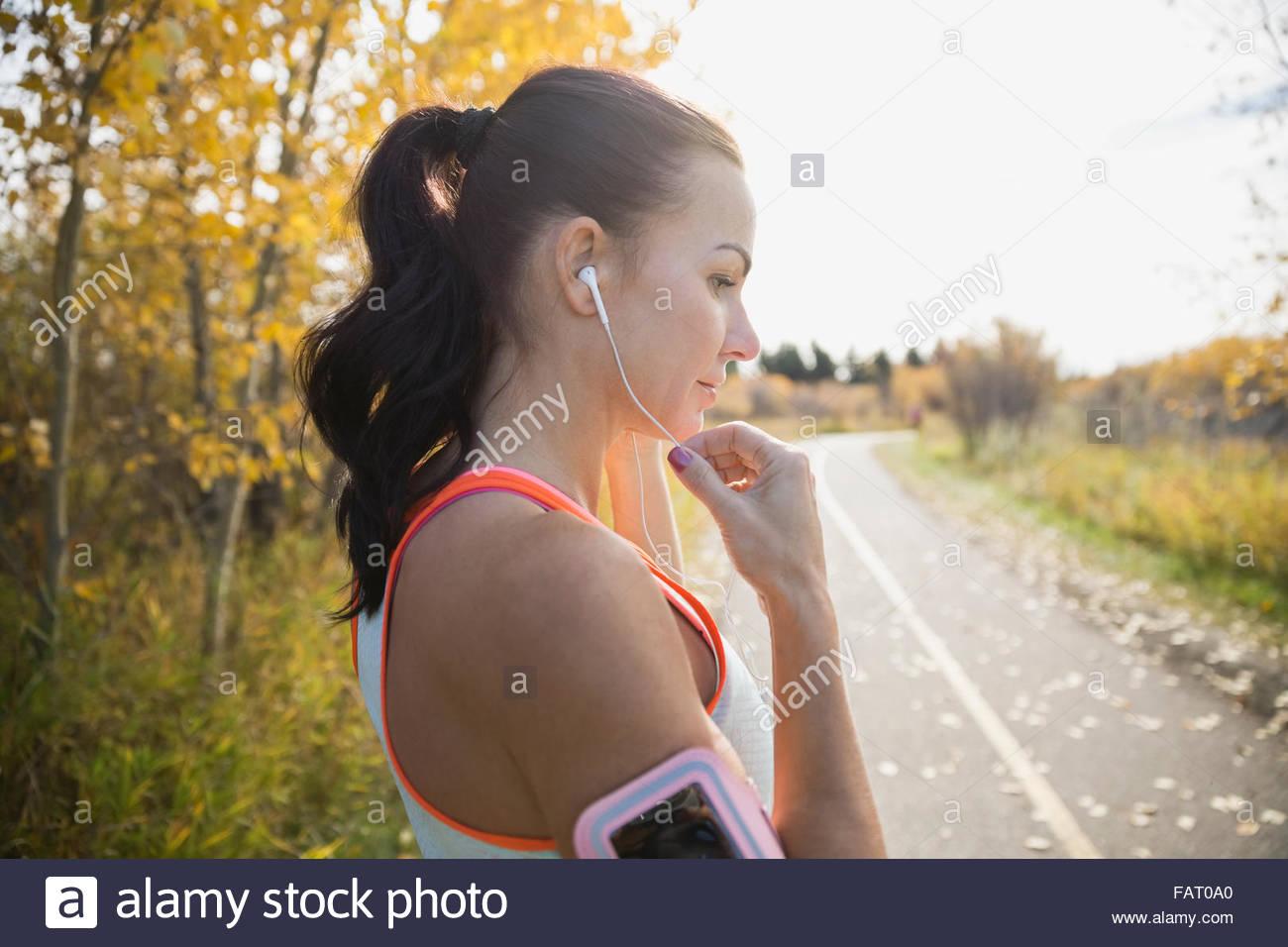 Pareggiatore con cuffie e fascia per il braccio sul percorso di autunno Immagini Stock