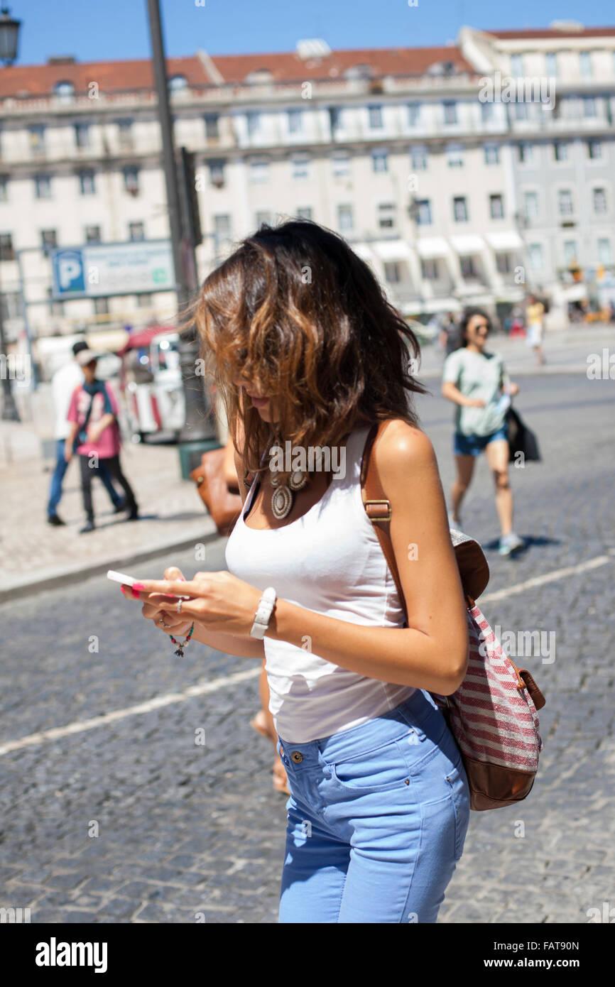 Guardando al telefono cellulare. Immagini Stock
