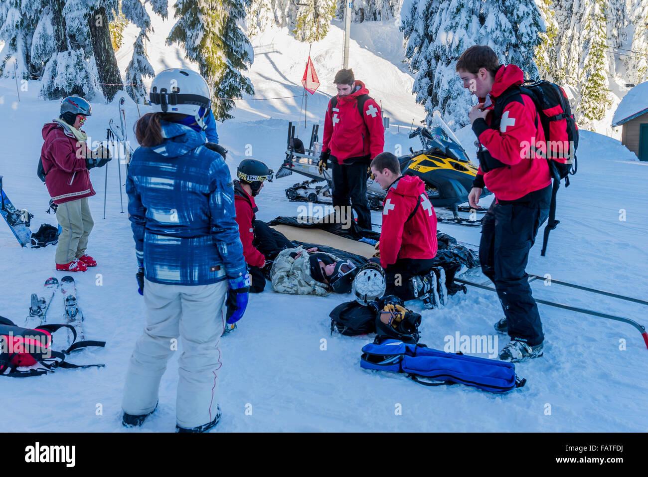 Primo soccorso gli operatori help feriti sciatore snowboarder, Mount Seymour Provincial Park, North Vancouver, British Immagini Stock
