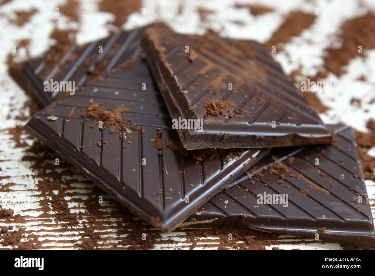 Pezzi di cioccolato fondente con cioccolato in polvere Immagini Stock
