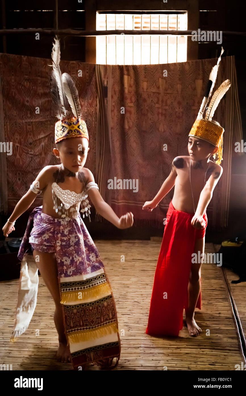 I bambini dei dayak Iban tribù dancing interno longhouse comunale. Immagini Stock