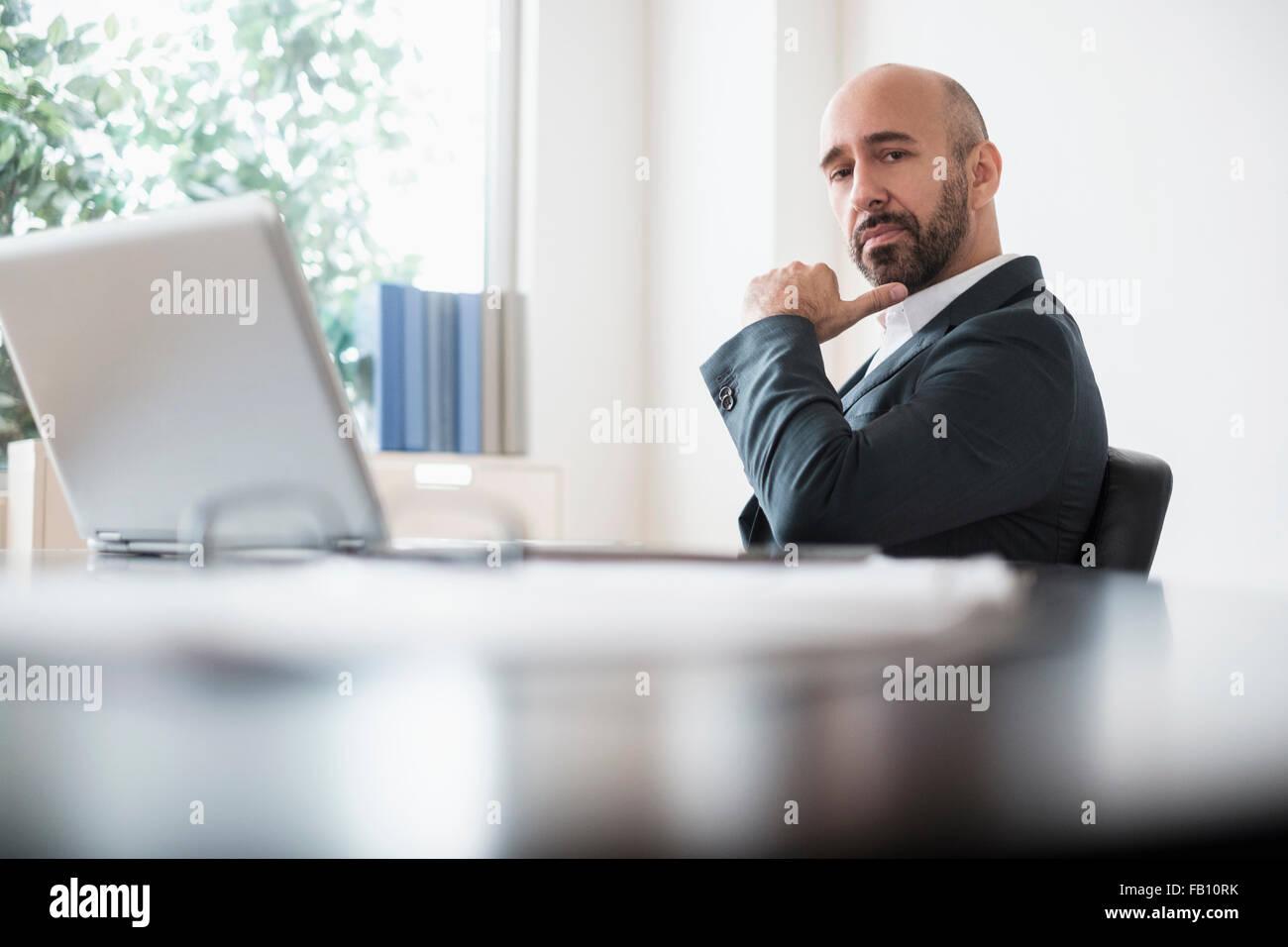 Imprenditore serio seduto alla scrivania in ufficio Immagini Stock