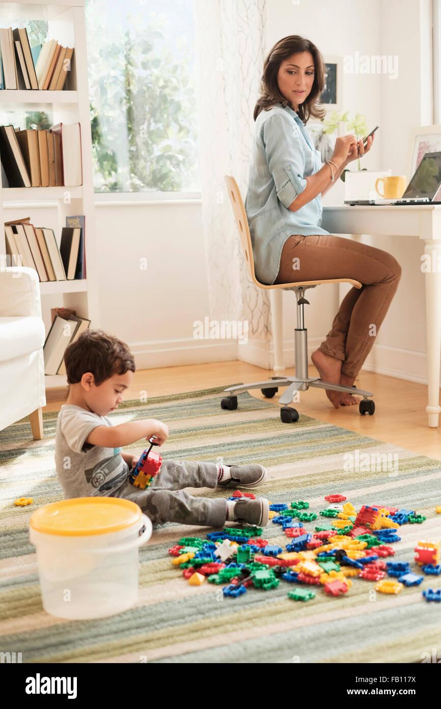 Ragazzo (2-3) giocando con blocchi giocattolo mentre la madre lavora sul computer portatile Immagini Stock