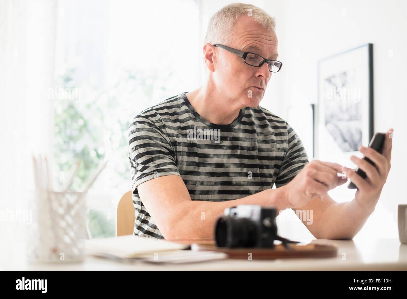 Uomo in ufficio a casa utilizza lo smartphone Immagini Stock