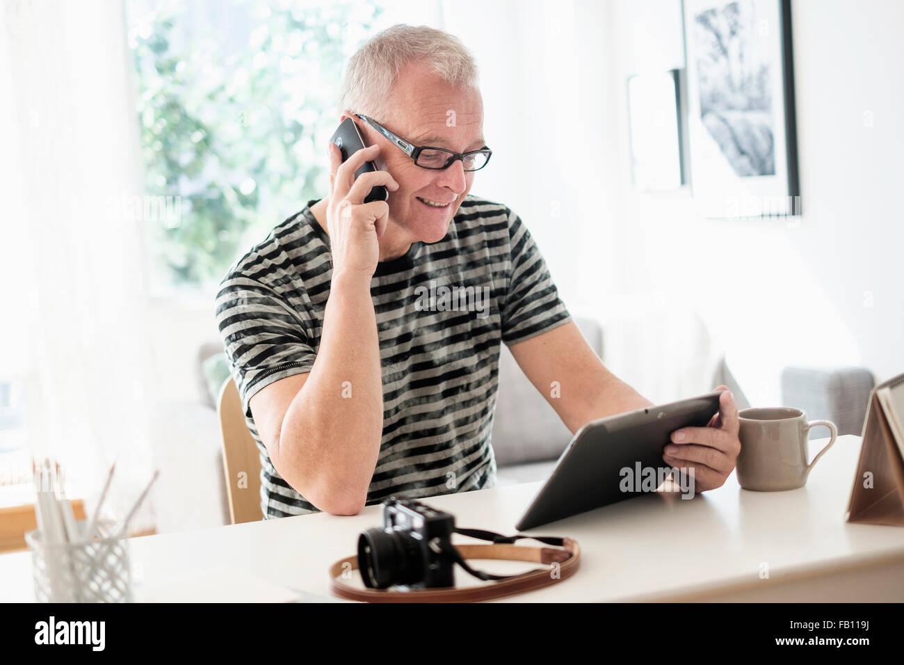 Uomo in ufficio a casa utilizzando lo smartphone e tablet Immagini Stock