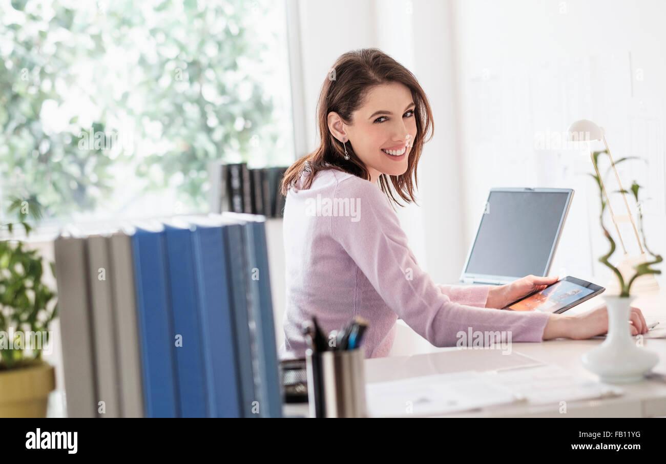 Giovane donna con tavoletta digitale, guardando la fotocamera Immagini Stock