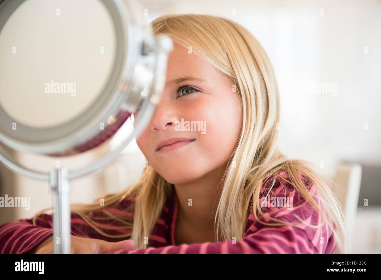 La ragazza (6-7) guardando lo specchietto di cortesia Immagini Stock